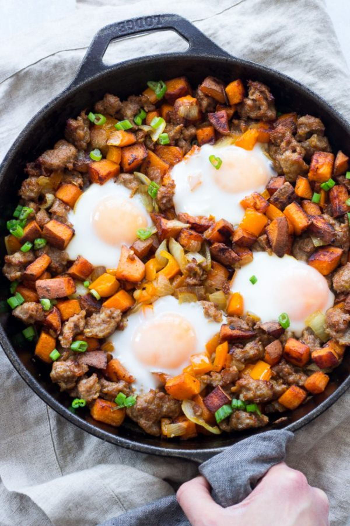 a skillet with sweet potato hash and fried eggs