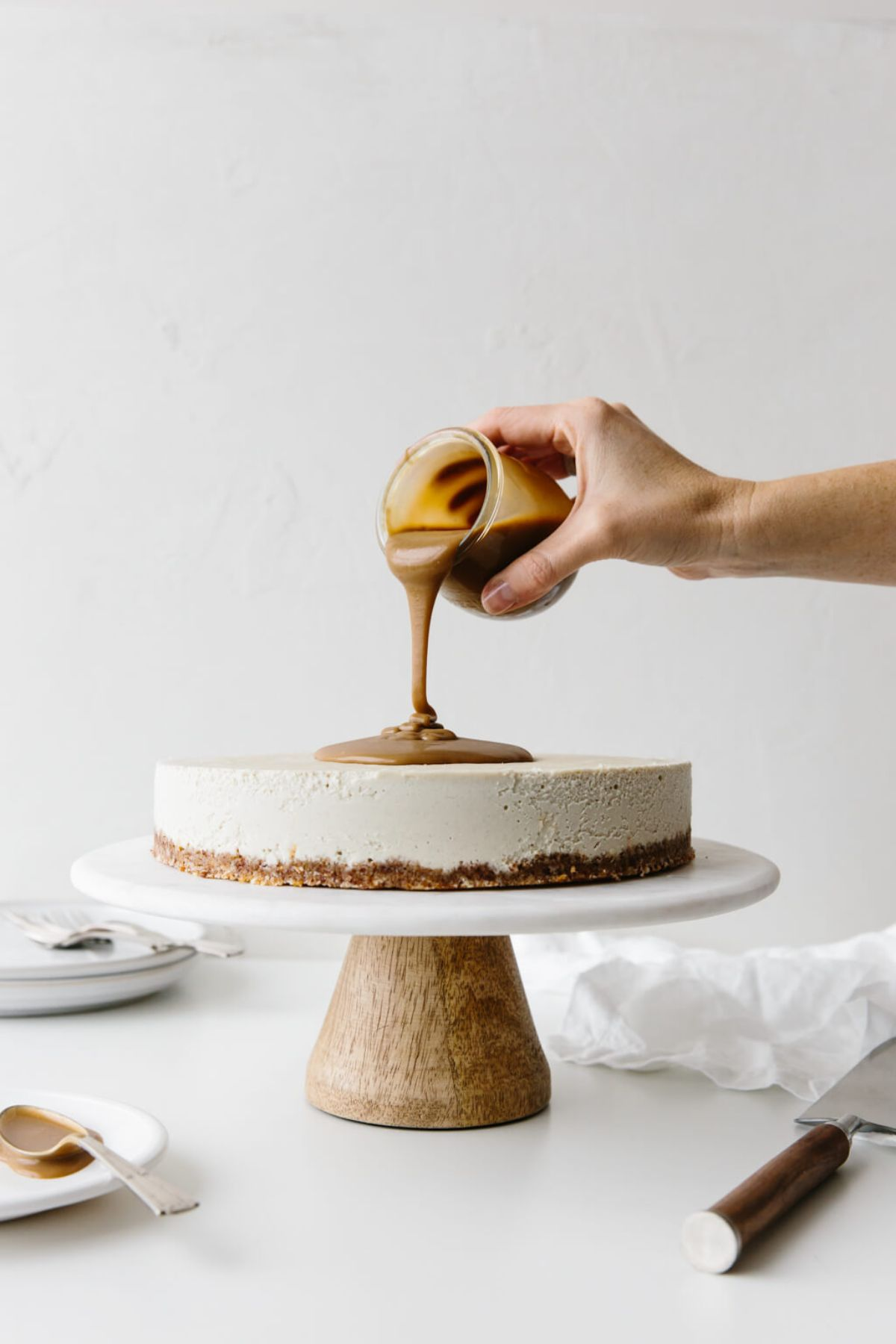 a cake stand with a vanilla cheesecake on it. A hand is pouring caramel sauce from a jar onto the top