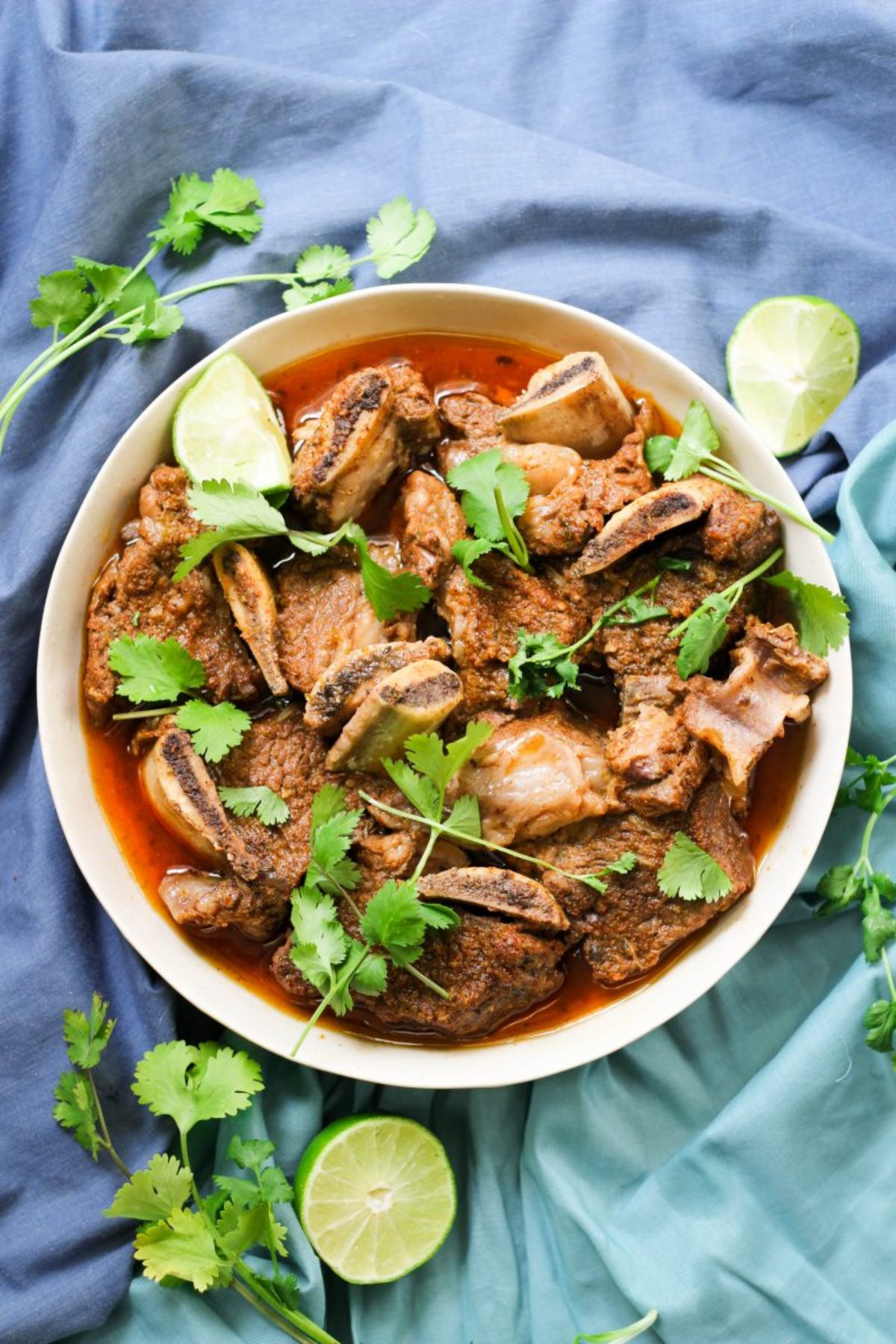 On a blue, ruffled cloth is a round white bowl filled with short rib stew and sprinkled with lime wedges and parsley
