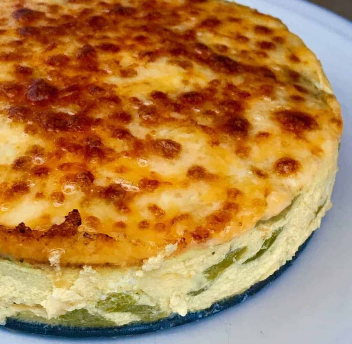 a partial shot of a fritatta with green beans in it and a caramalised cheese top