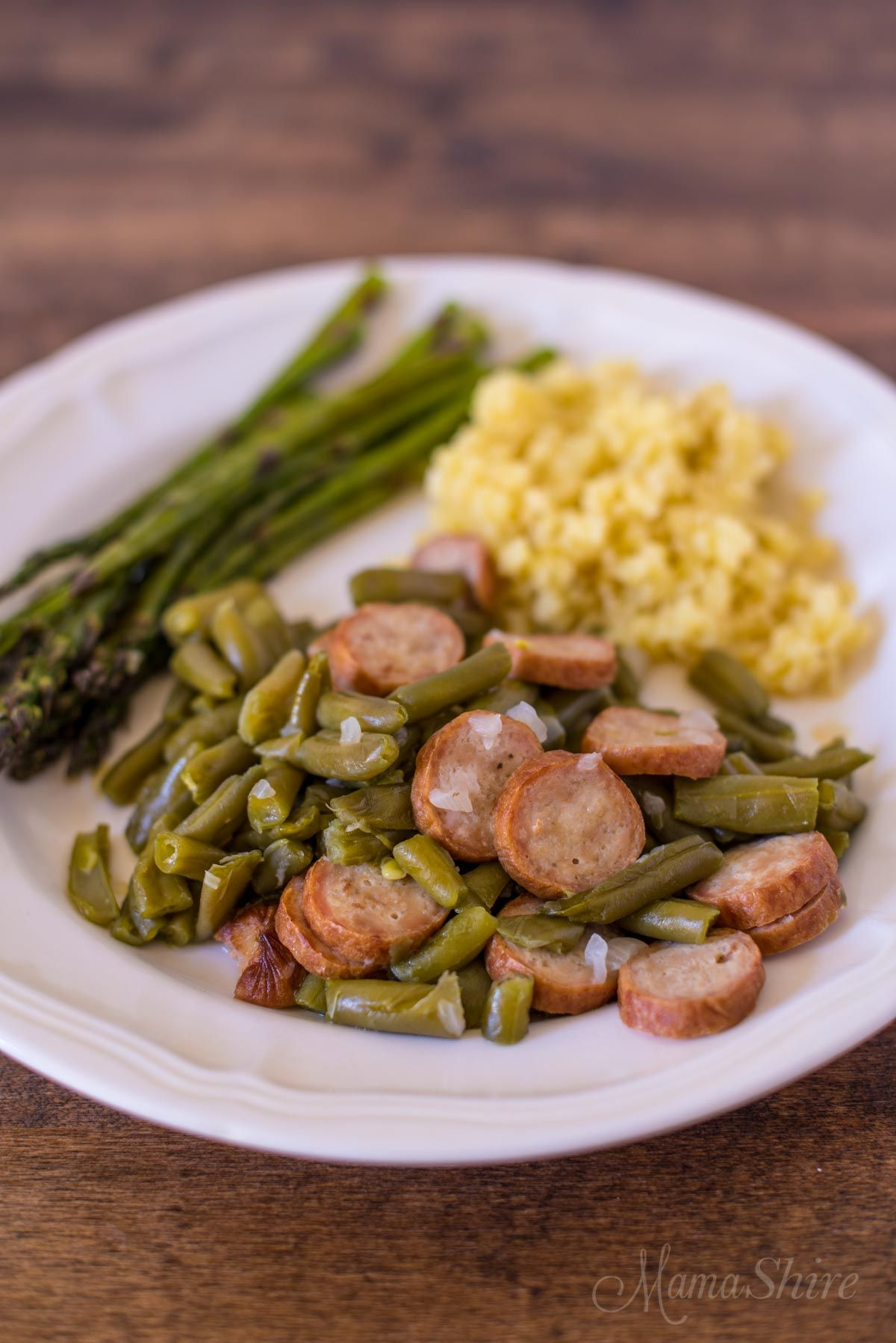 A dark wooden table with a white plate on it. On the plate is a bundle of asparagus, yellow rice, and sausage and beans