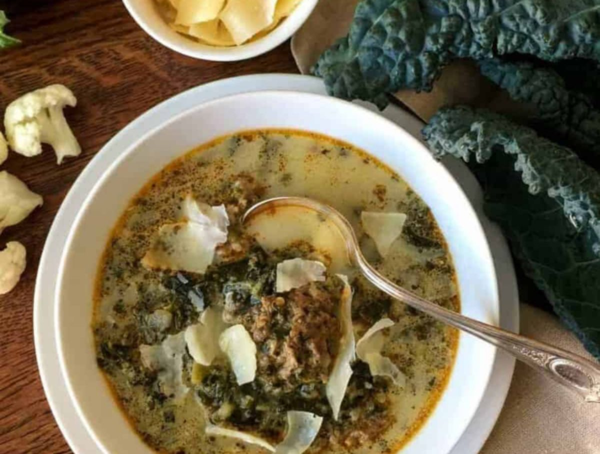 On a wooden table is a white bowl with sausage and kale soup in it, and a silver spoon ain in it. On the right are some leaves of kale, on the left are some florets of cauliflower