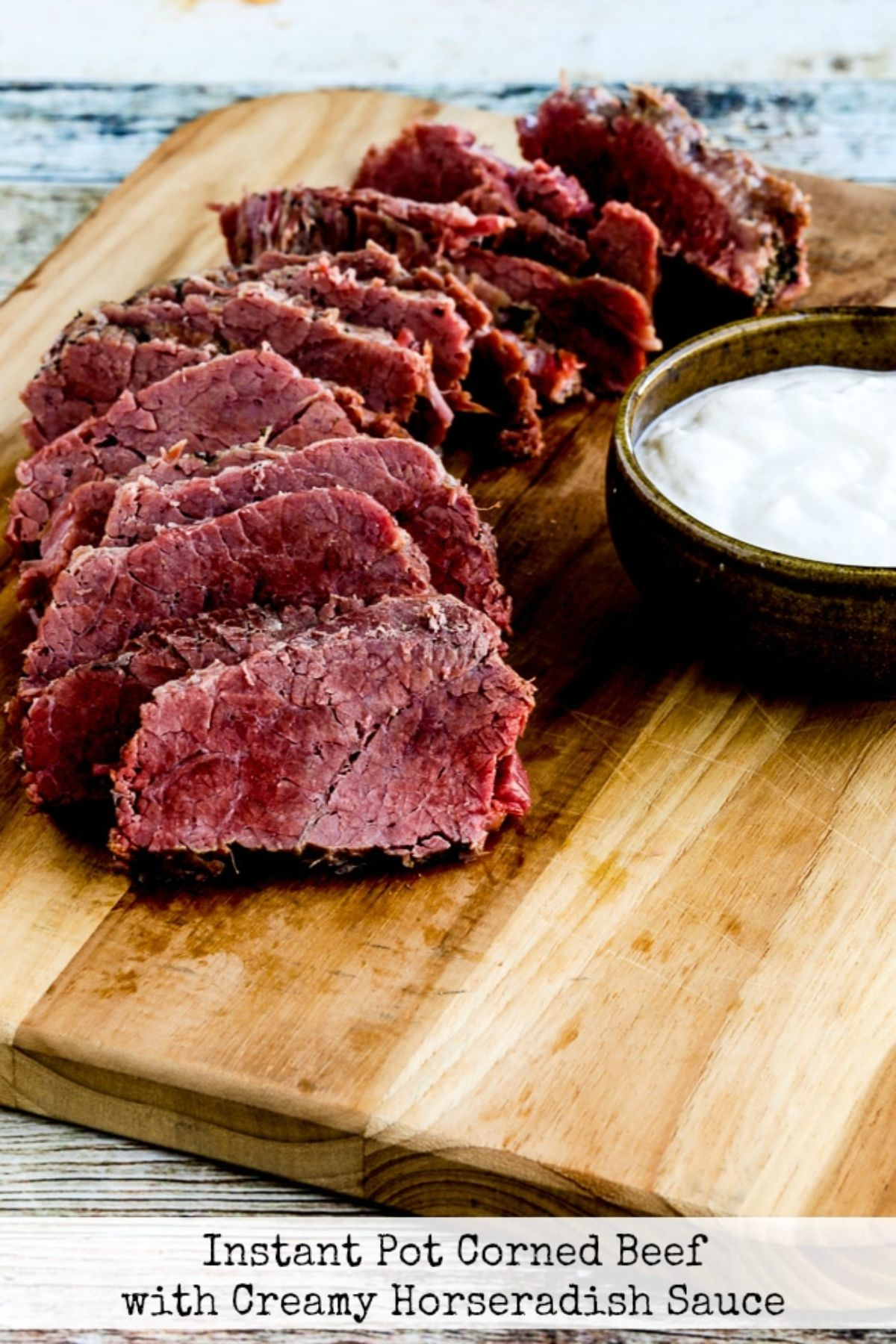 ON a wooden board are slices of beef laid out on top of each other. To the right is a round dish filled with horseradish sauce