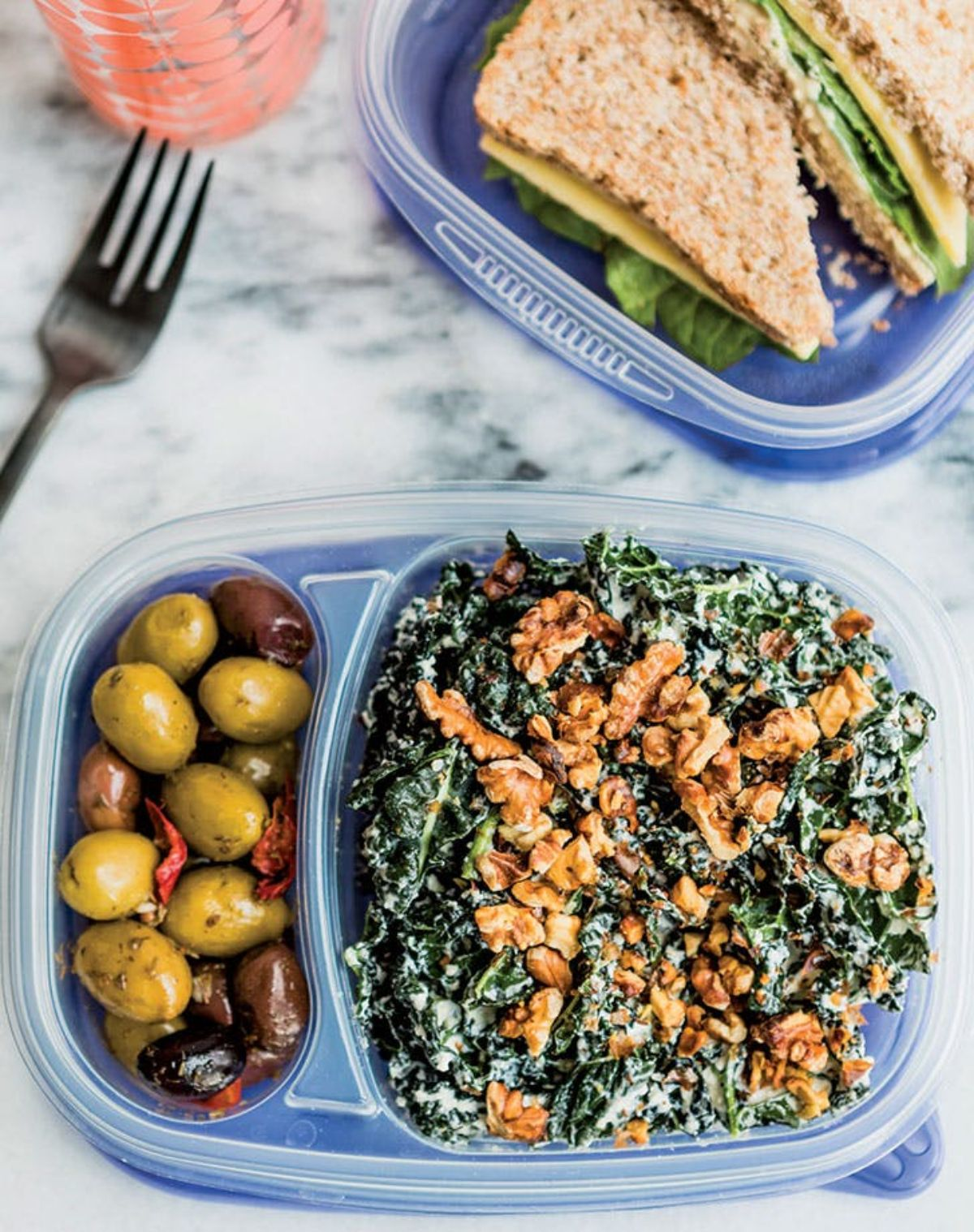 On a white marble countertop are two open blue plastic lunchboxes. Kale salad with walnuts is in the section on the right and mixed olives on the left. The second box behind it is partialy in shot and holds a cheese and lettuce sandwich