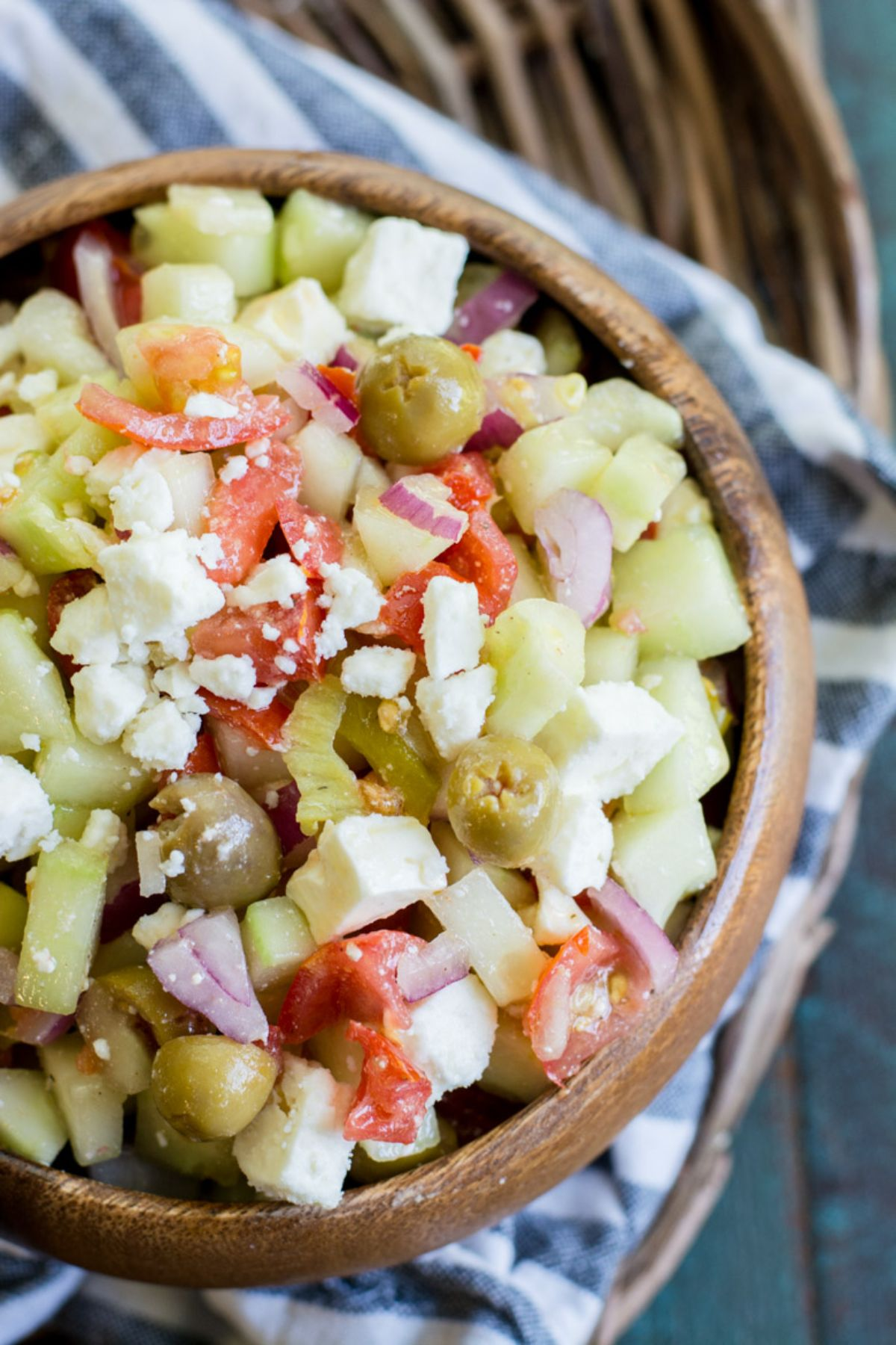 On a blurred wicker table is a bue and white striped cloth. On top of that is a round wooden bowl filled with cucumber salald topped with crumbled feta