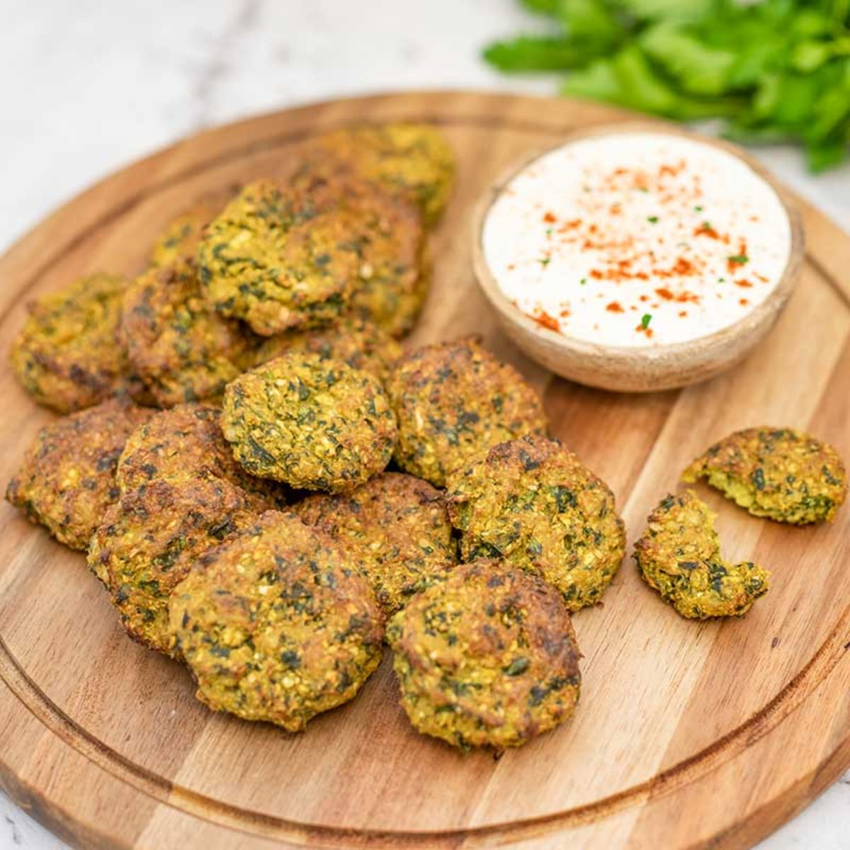 On a whote countertop is a round wooden board. On this is a pile of felafel, and a small bowl of white dip topped with paprika