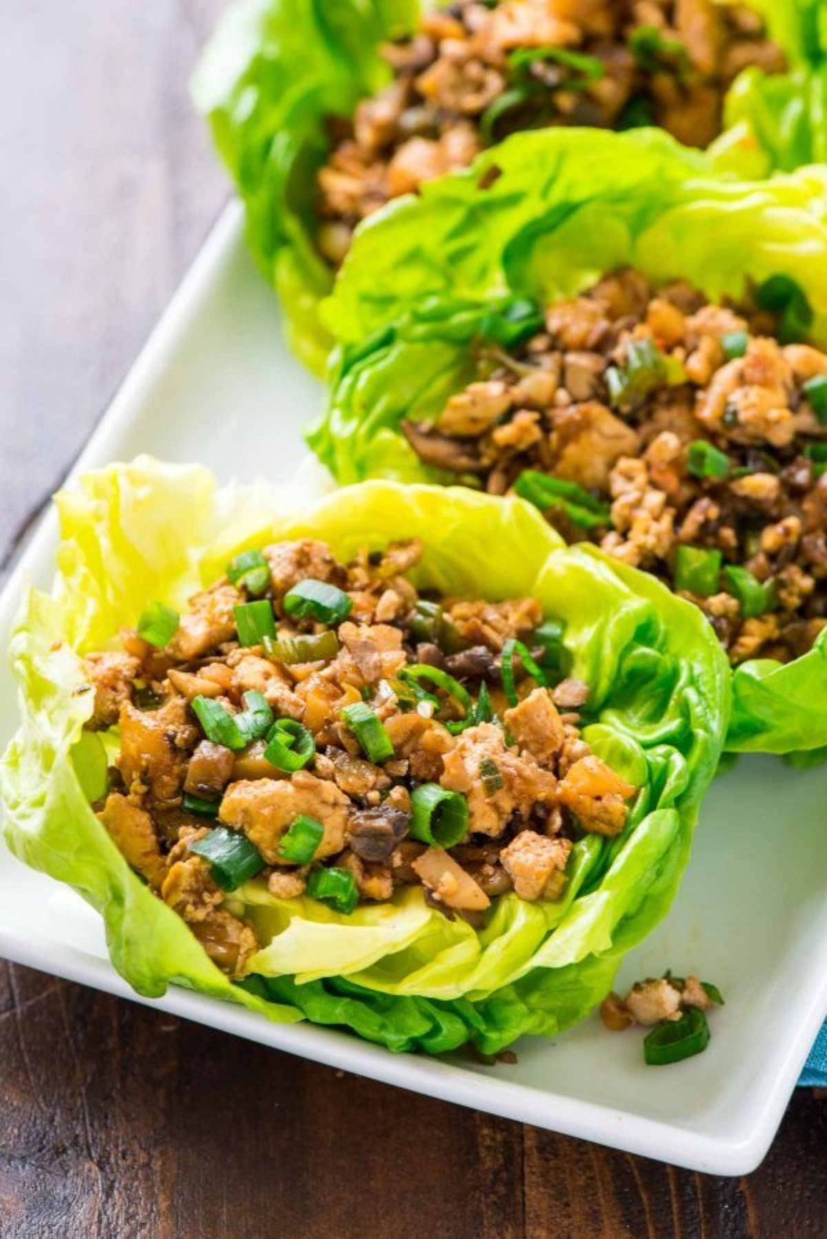On a dark wooden table is a partial shot of a rectangular white plate. On this are lettuce cups filled with bean and vegetable mix