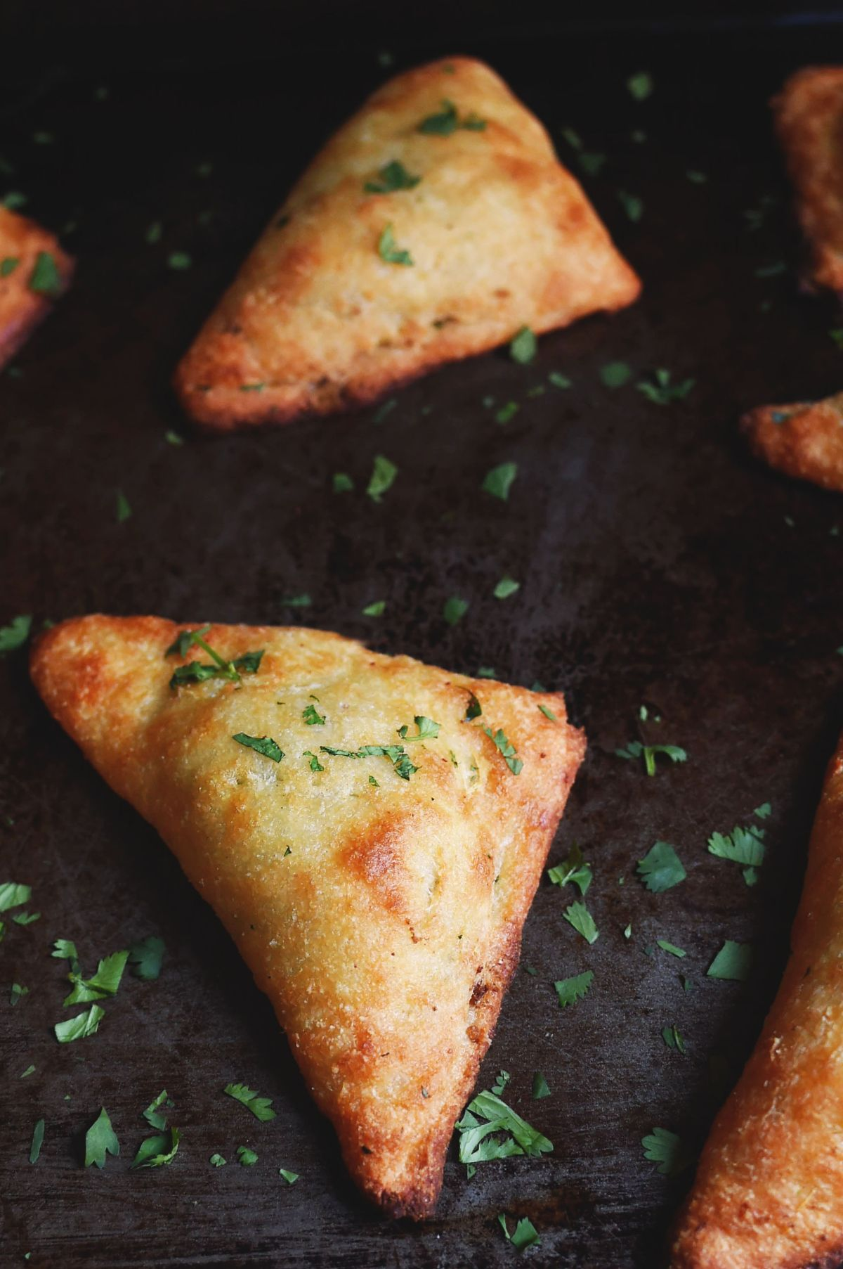 A partial shot of a skillet with 2 vegetable samosas sprinkled with chopped herbs
