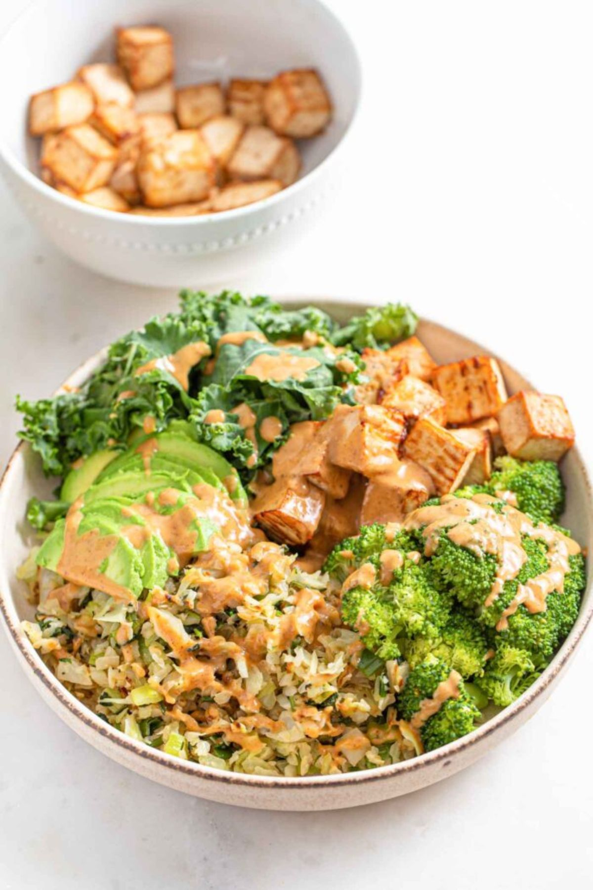 In the foreground is a white bowl with a dark stripe around the rim. Inside are sections of broccoli, fried tofu, kale, avocado and rice, all toppped with an orange sauce. Behind and blurred is a smaller white bowl filled with the tofu