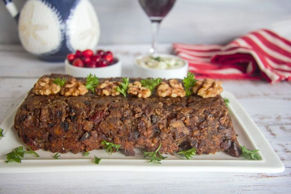 On a whitewashed table is a rectangular board with a wwalnut loaf on top, topped with shelled walnuts and parsley. Behind and blurred are two bowls of cranberries and a white sauce, a glass of red wine, a patterned jug, and a red and white striped towel