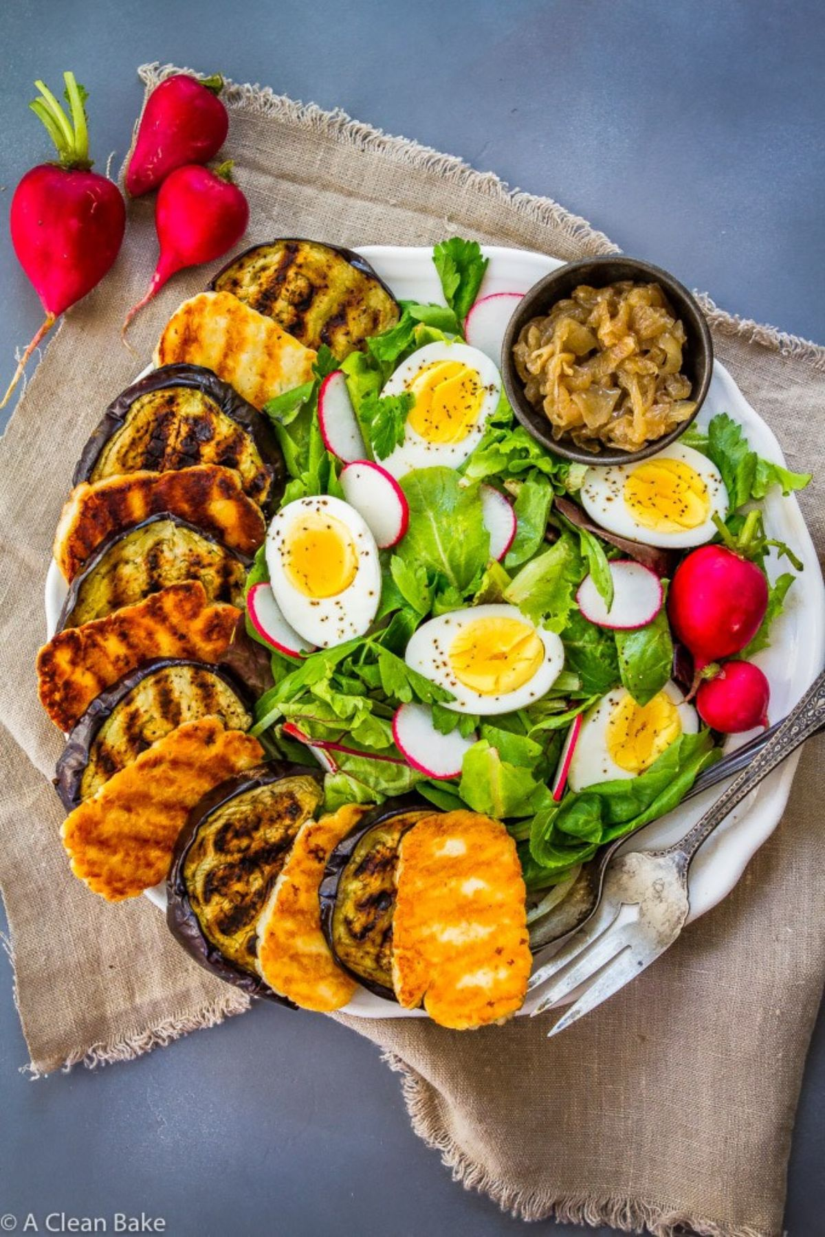 ON a blue counter is a hessian cloth. On top of this is a white round plate with layers of fried eggplant and halloumi on the left, and salad leaves radishes and halved boiled eggs on the right. A small pot of pickle sits at the top of the plate. To the left are 3 radishes