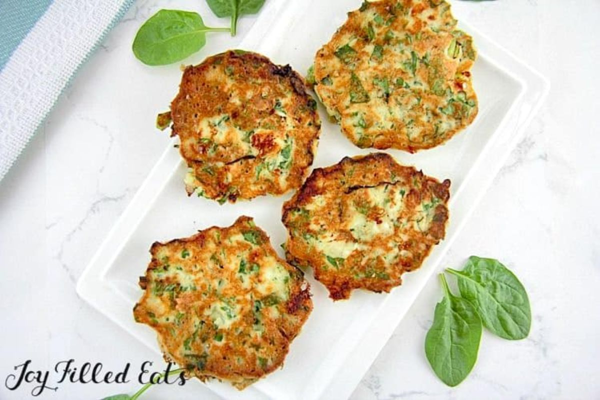 On a white countertop is a white rectangular dish with 4 spinach and feta pancakes on it. Basil leaves are scattered around