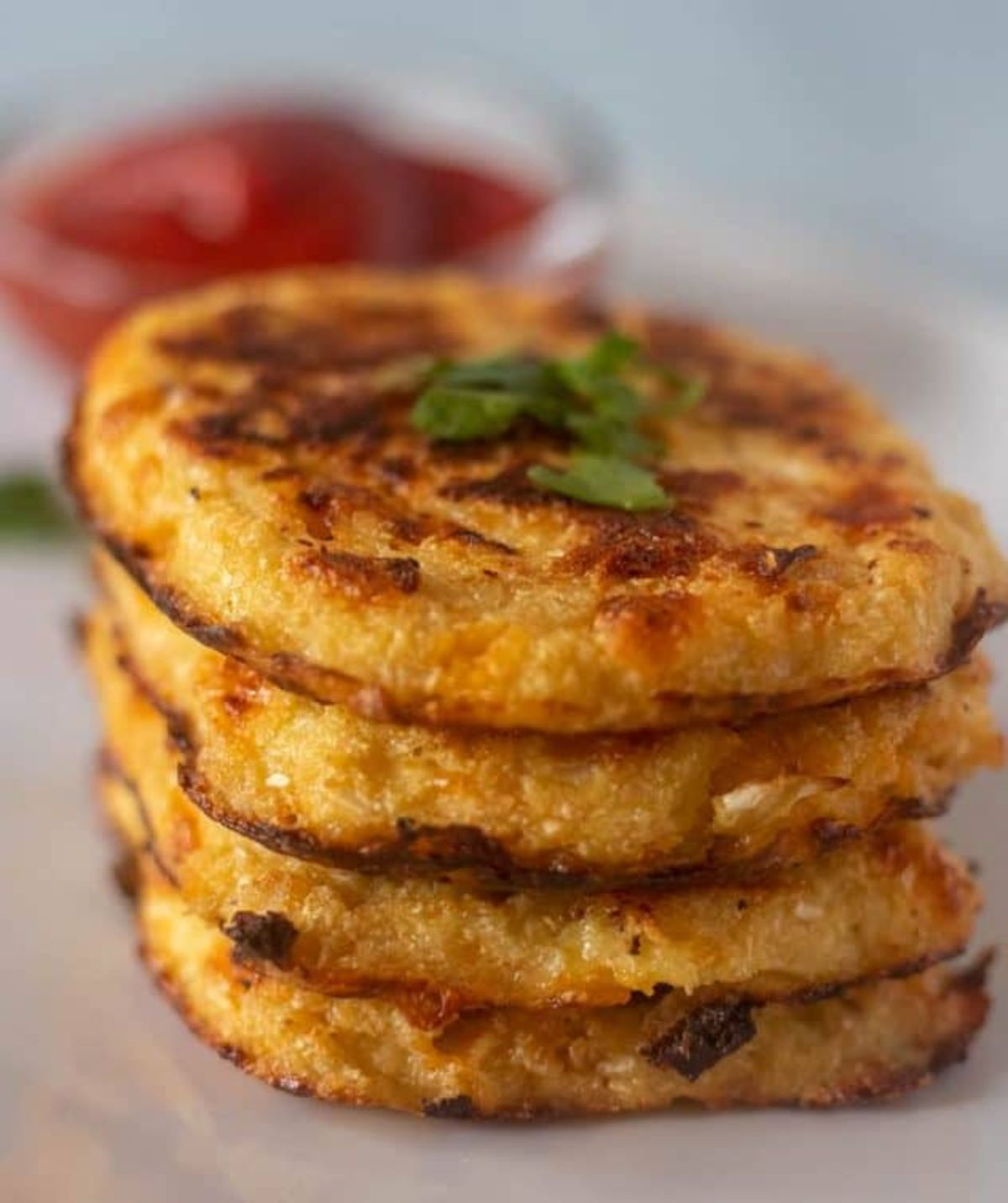 WIth a blurred background of a pot of red sauce, a stack of four hash browns with chopped herbs on top