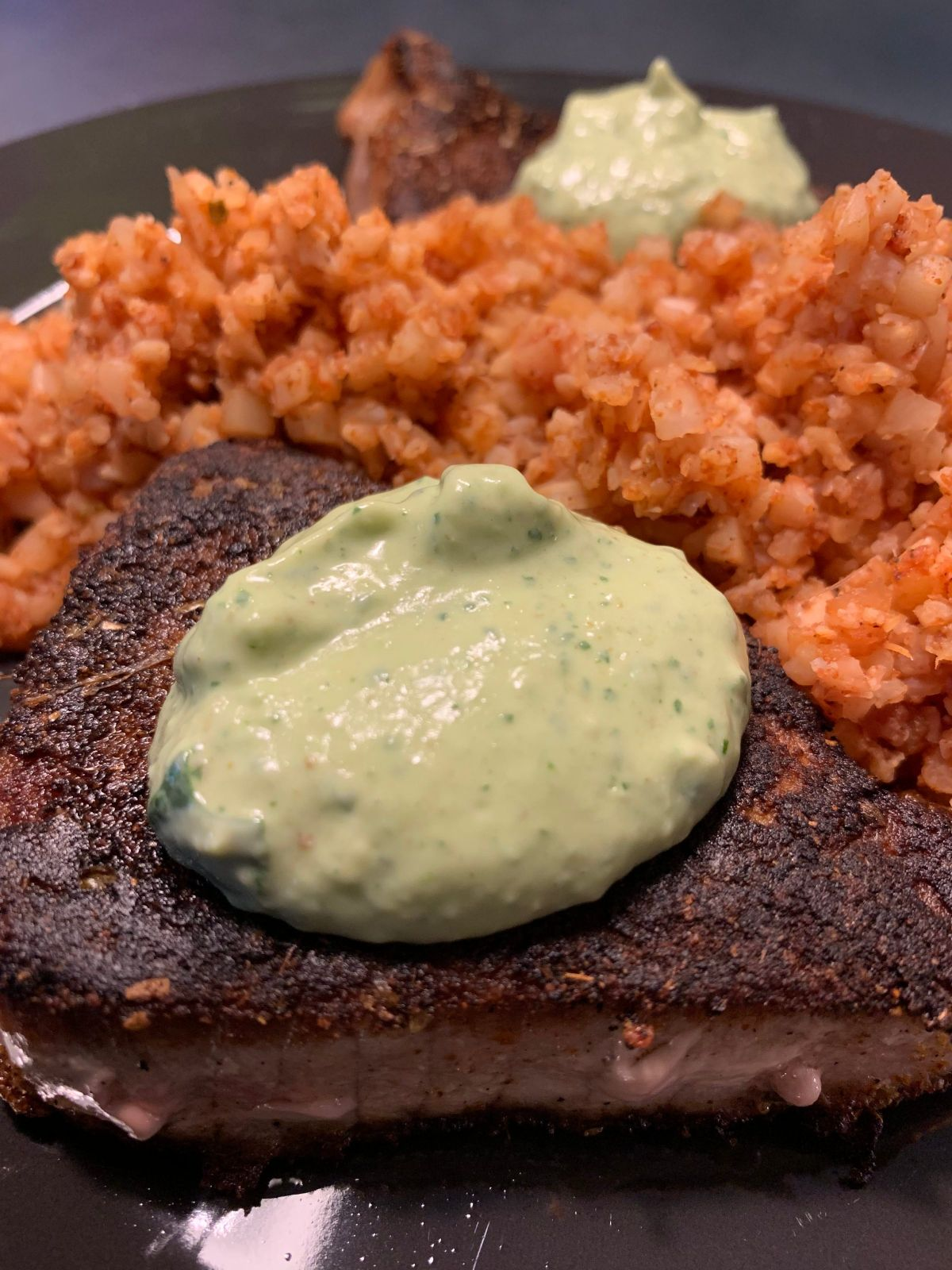A partial shot of a dark gray plate with tomato cauliflower rice, seared tuna and a creamy sauce on top