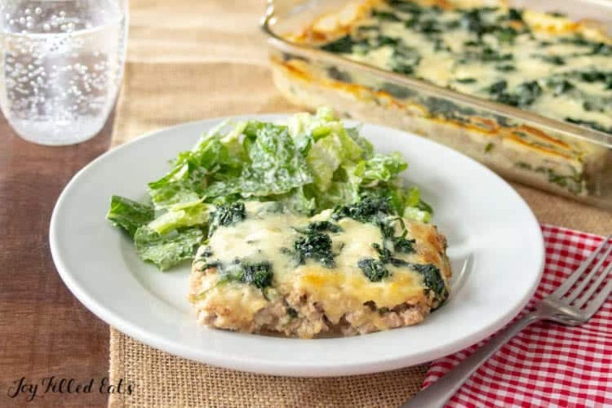 On a wooden table, surrounded by a glass of water, and a lurred shot of a rectangular casserole dish filled with creamy spinach casserole, is a square portion of the casserole garnished with a side of green lettuce