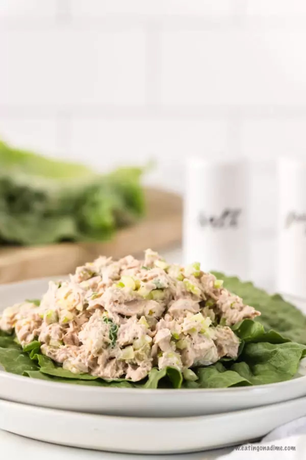 In the foreground is a stack of two white plates with lettuce leaves piled with tuna salad, Blurred in the background are some lettuce leaves on a wooden board and white salt and pepper shakers