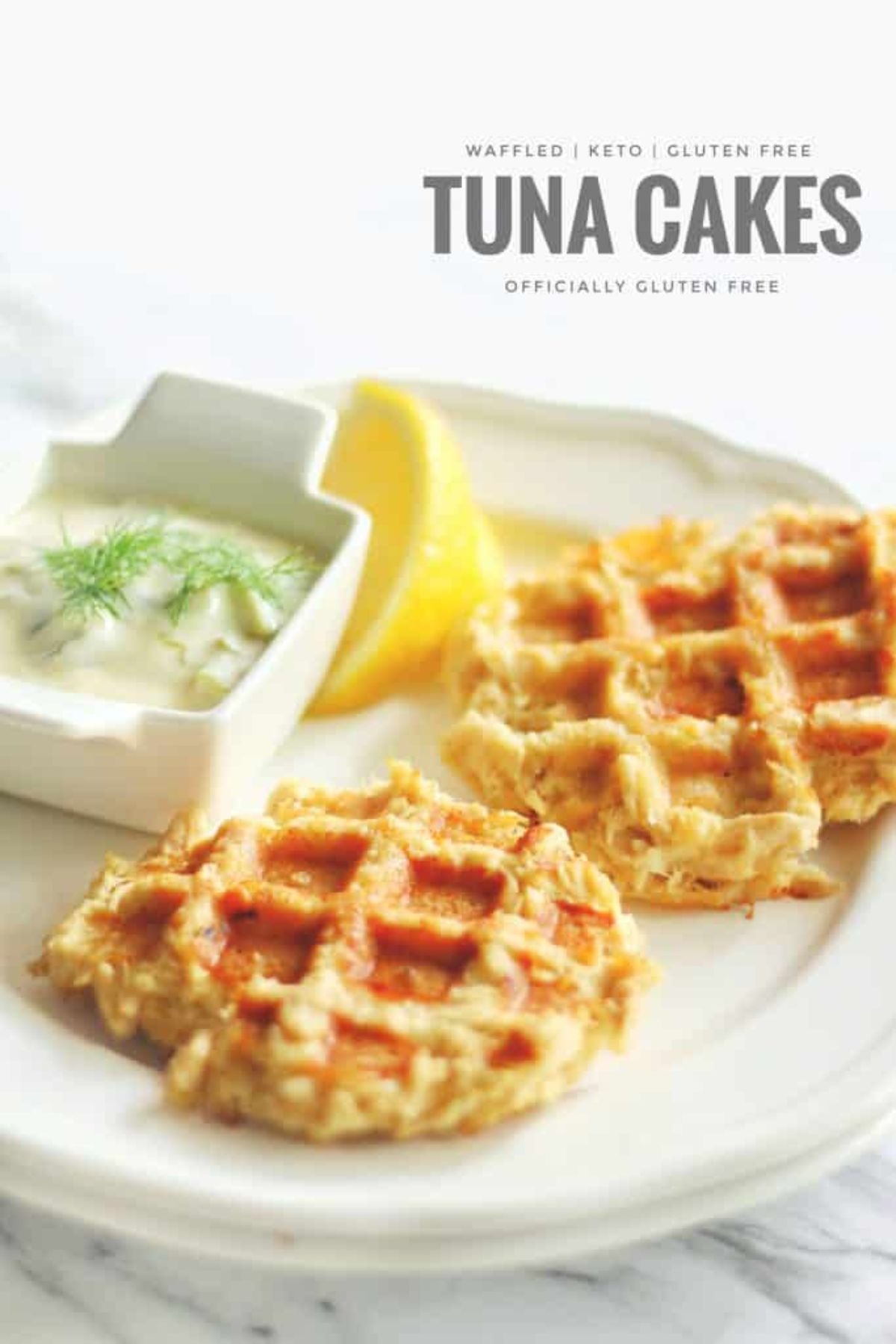 "The text reads ""Waffled, Keto, Gluten-free Tuna cakes. Officially gluten-free"" On a white marbled surface is a white plate with two waffles, a lemon slice and a square pot full of white sauce"