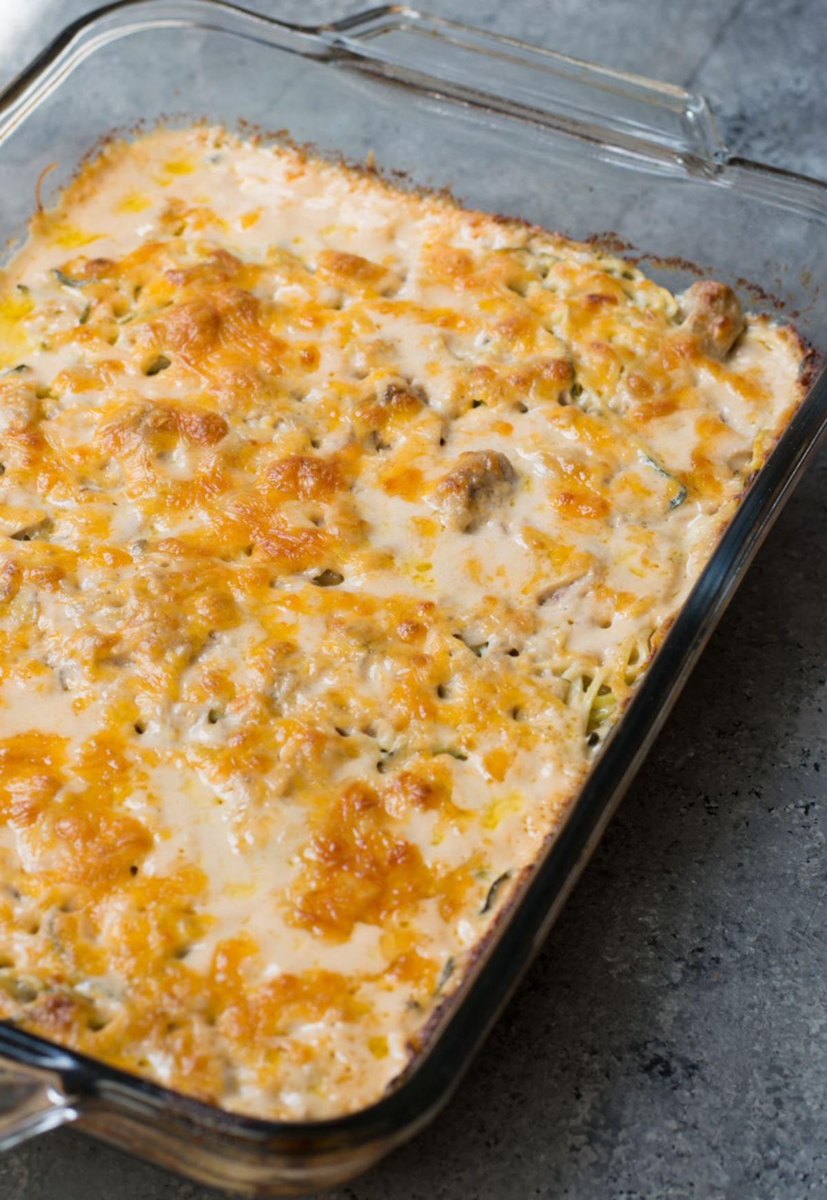 On a gray surface is a rectangular casserole dish filled with cheese-topped casserole