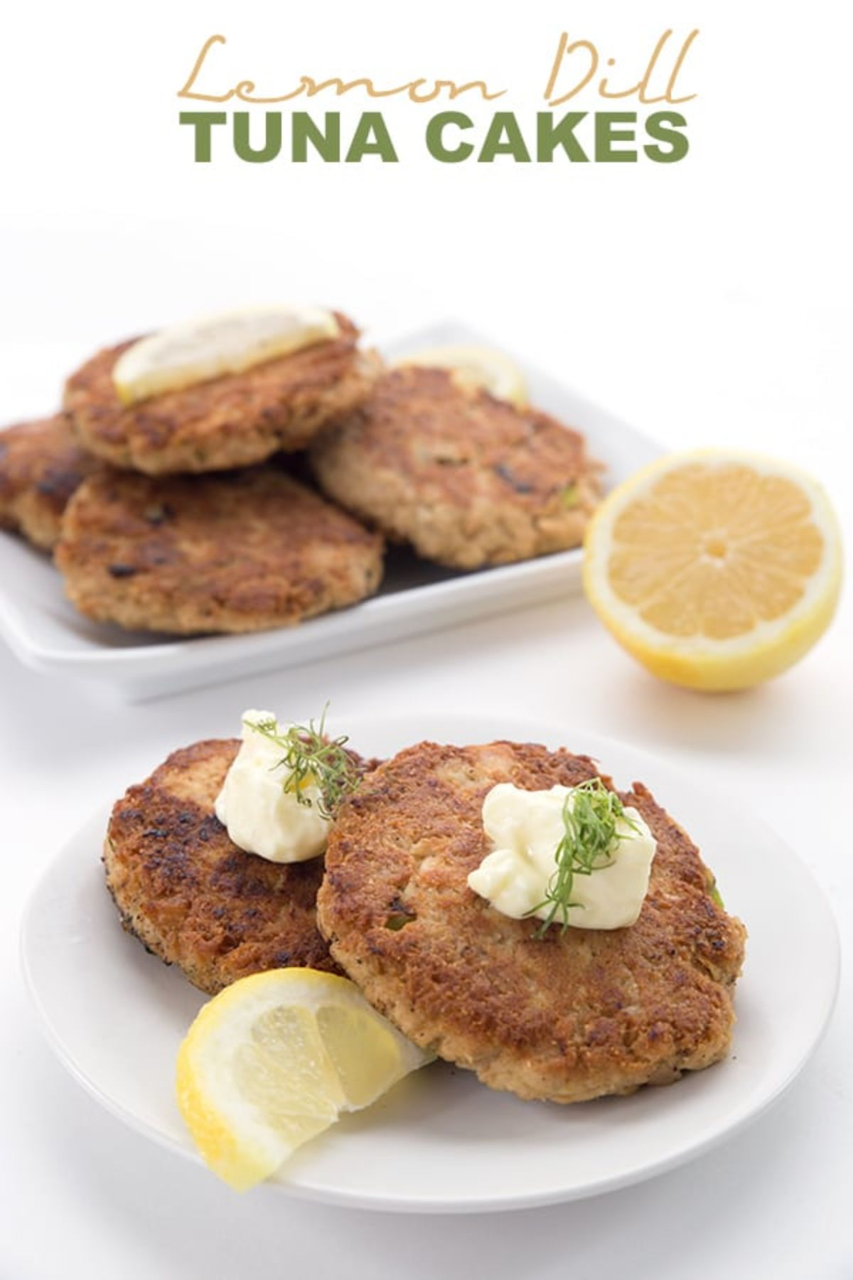 "The text reads ""Lemon Dill Tuna Cakes"". The photo is of one square and one round white plate filled with tuna cakes and topped with sour cream and dill, garnished with lemon"