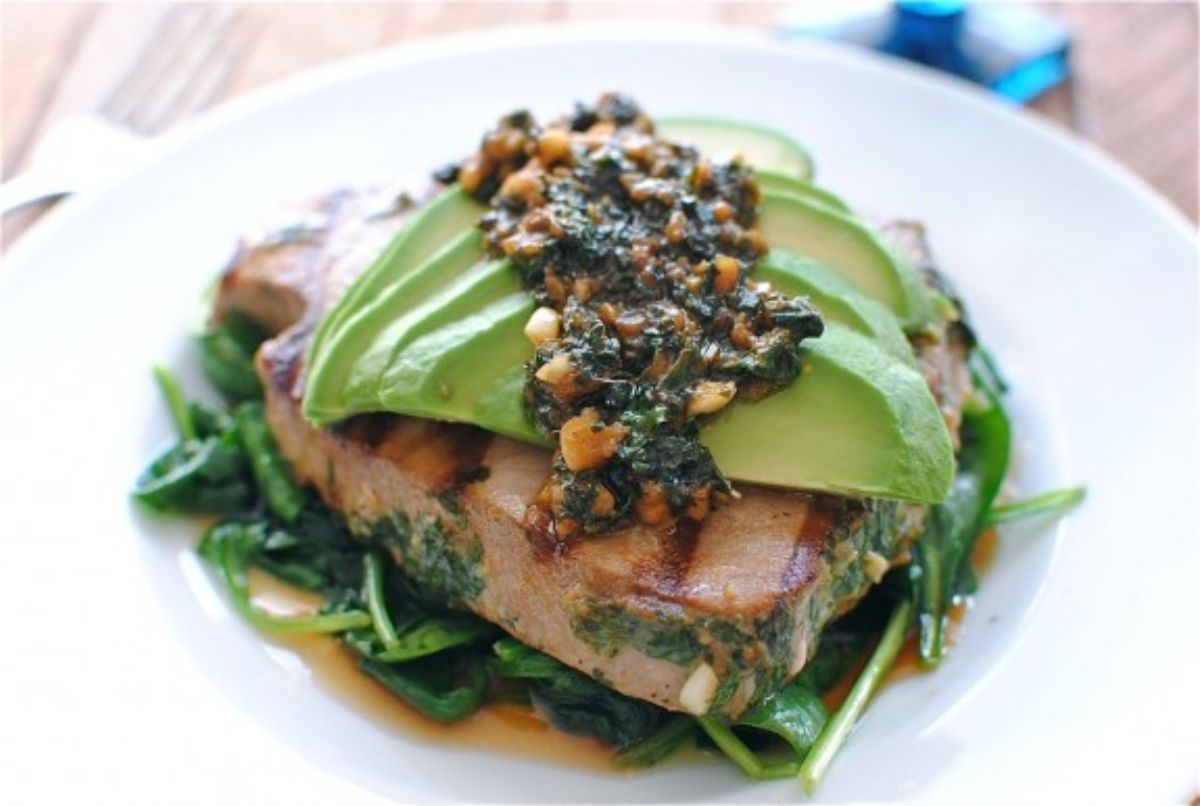 A white round plate with wilted spinach, seared tuna steak, sliced avocado and pesto