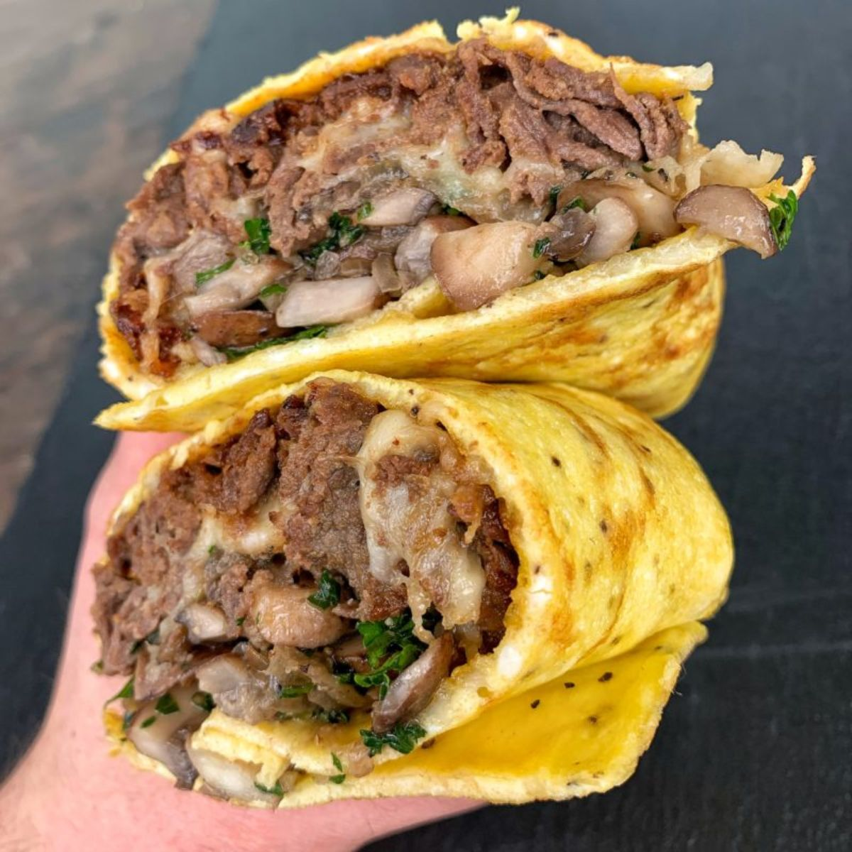 A hand holds two halves of an egg burrito filled with steak and vegetable mix