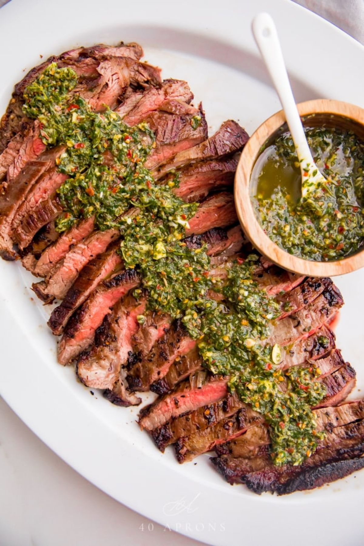 An oval white plate holds slices of rare steak, drizzled over with chiichurri sauce. A wooden pot of the sauce sits on the right of the plate with a white spoon in it