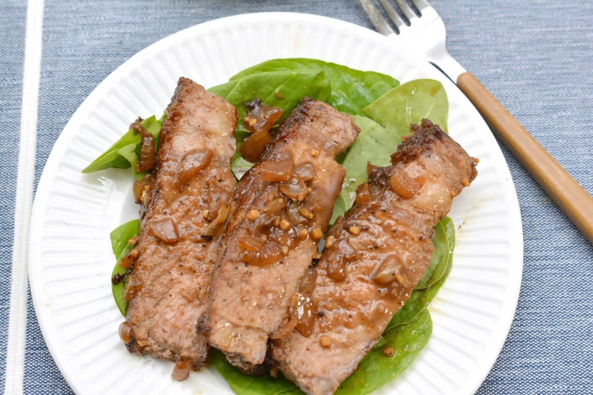 A round white plate sits on a blue cloth. On the plate is a bed of leaves wth 3 clices of steak on top. To the right of the plate is a wooden handled fork