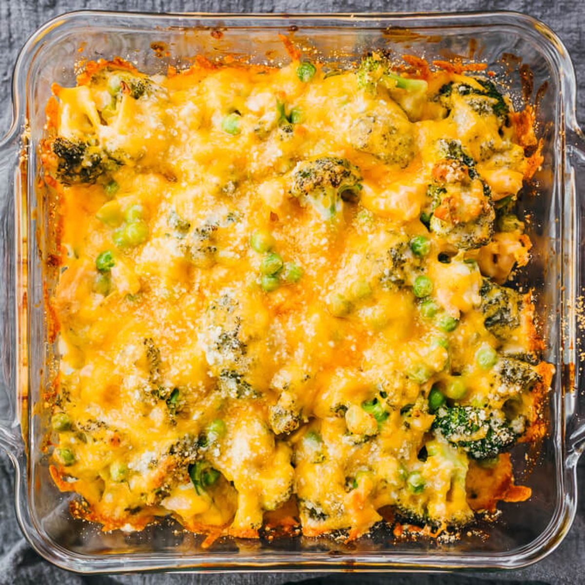 on a gray cloth is a square galss casserole dish filled with cheese-topped casserole. Peas and broccoli can just be seen