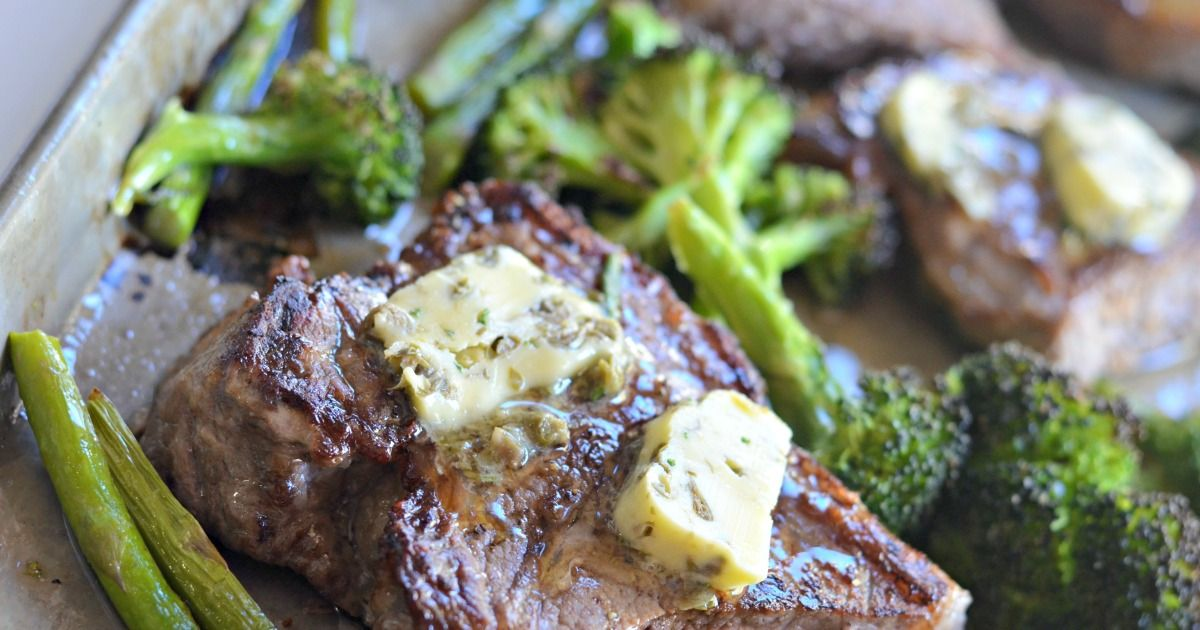 A partial shot of a baking tray filled with broccoli florets and steak. On the steak are two slabs of garlic butter
