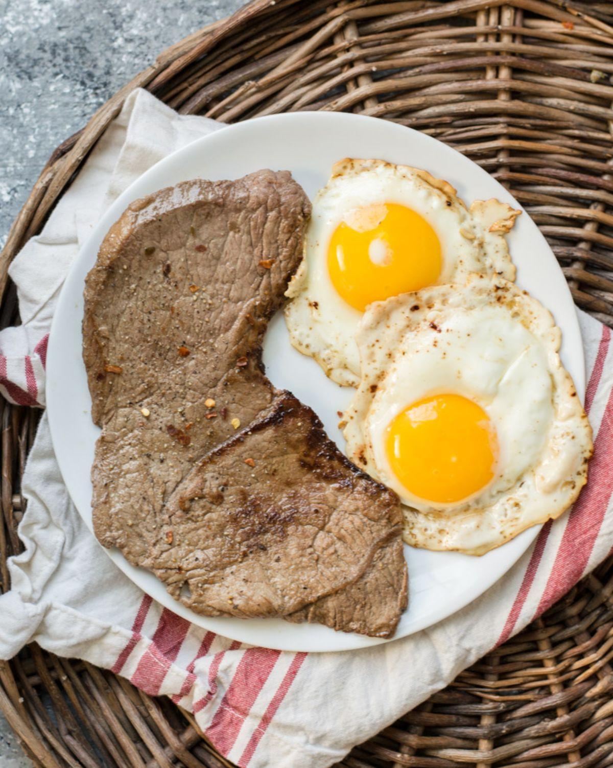 On a wicker tray is a white and red cloth, on which rests a white plate. On the plate is a large steak and 2 fried eggs.