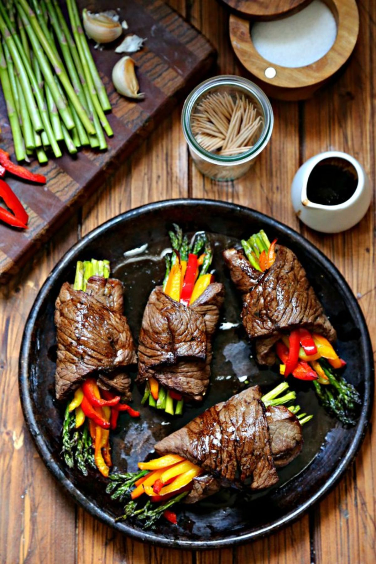 A dark wooden tale has a chopping board on the top left filled with asparagus, sliced peppers and garlic cloves. On the top right is a woodean bowl full of salt, a glass jar full of toothpicks and a white jug full of sauce. At the bottom fo the shot is a dark round plate with 4 bundles of asparagus and pepper wrapped in steak slices.