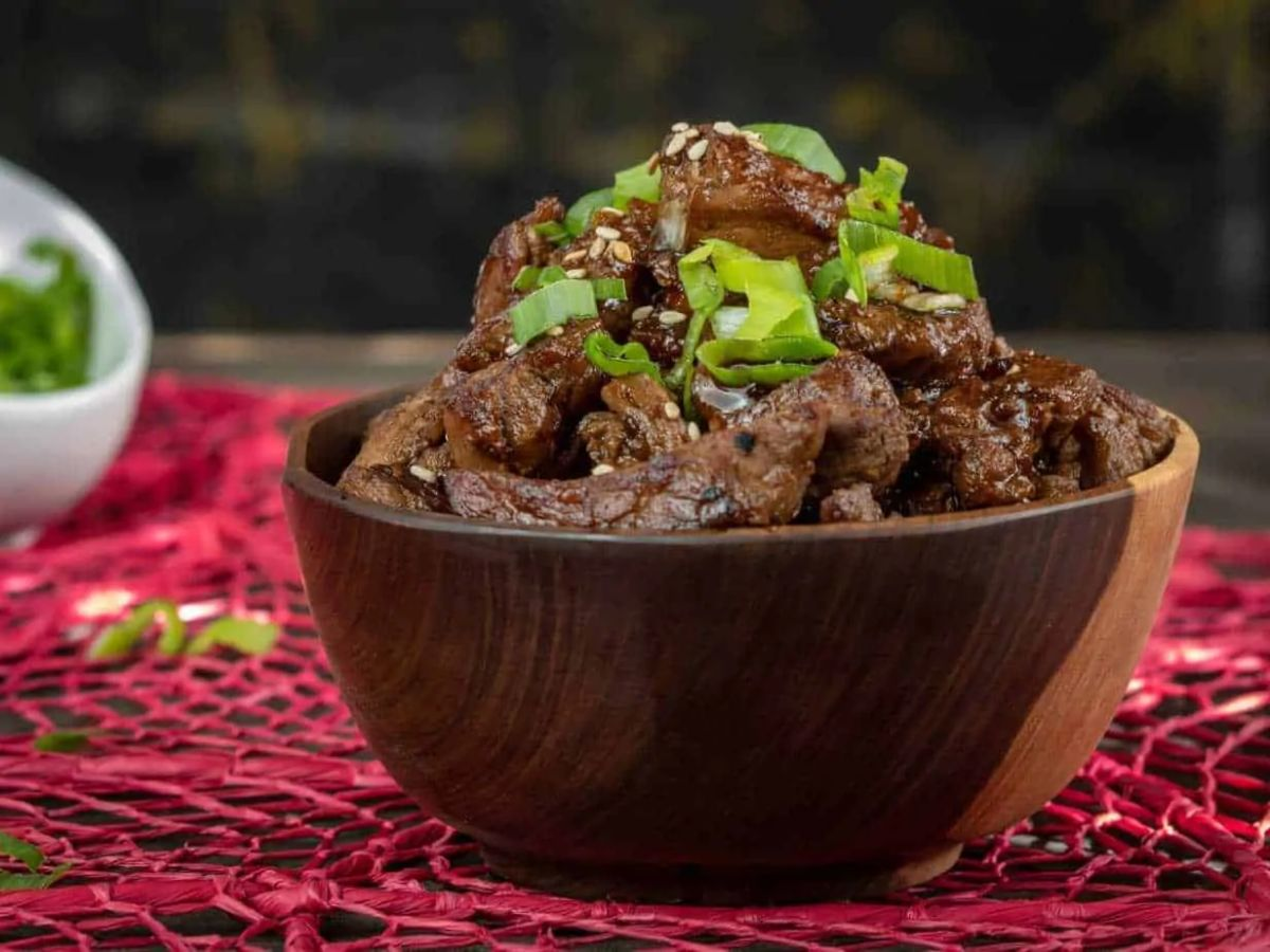 On a red patterened mat is a deep wooden bowl. In it are slices of beef toped with sesame seeds and sliced scallions