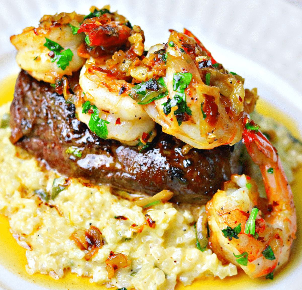 A close up of a pile of rice, steak and shrimp topped with a chilli and herb sauce