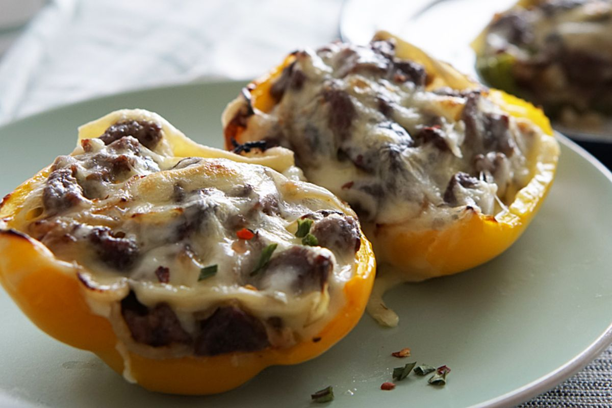 A white, oval plate holds 2 halves of a yellow pepper. Inside the halves is a cheesesteak mixture