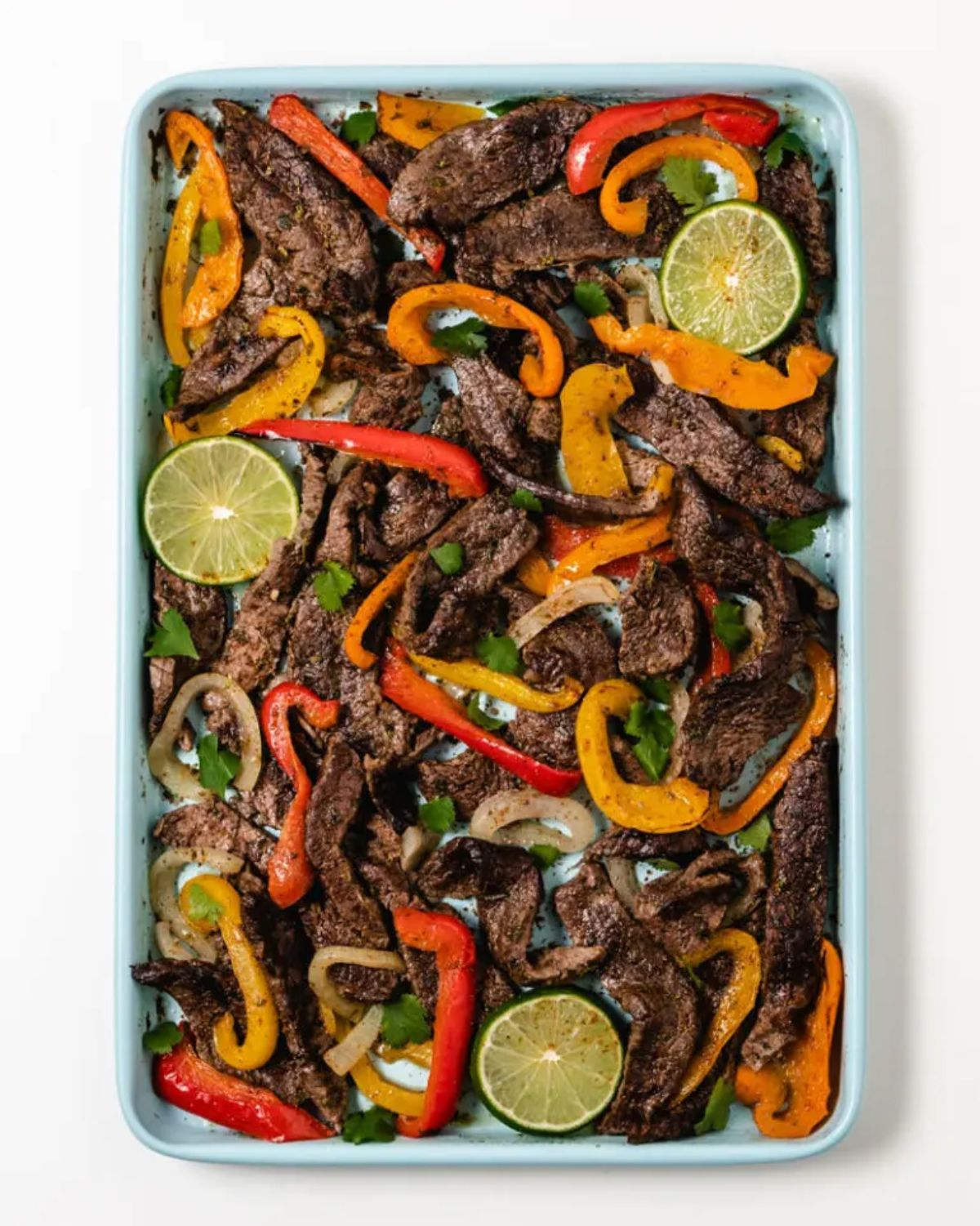 A rectangular roasting dish filled with steak slices, peppers, onions and lime slices.