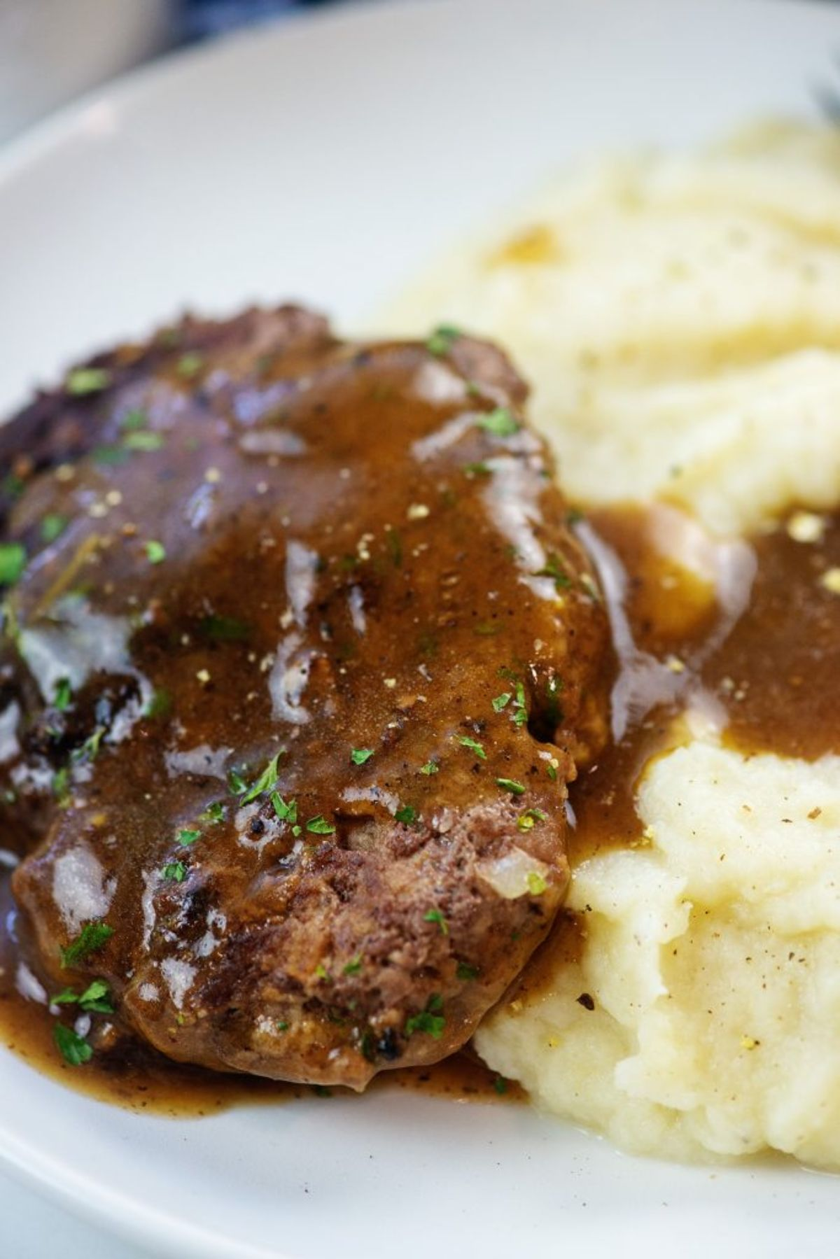 A partial close up of a steak in gravy, and mashed potato