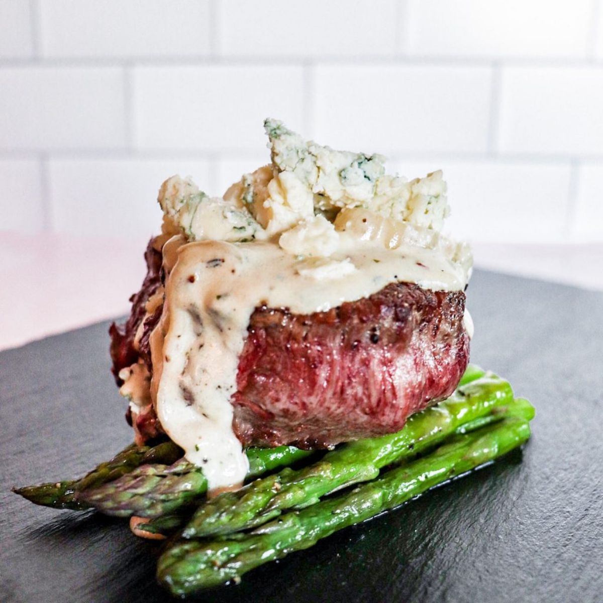 On a dark wooden board against a black background is a bunch of asparagus, with a thick steak on top, topped by a cheese sauce