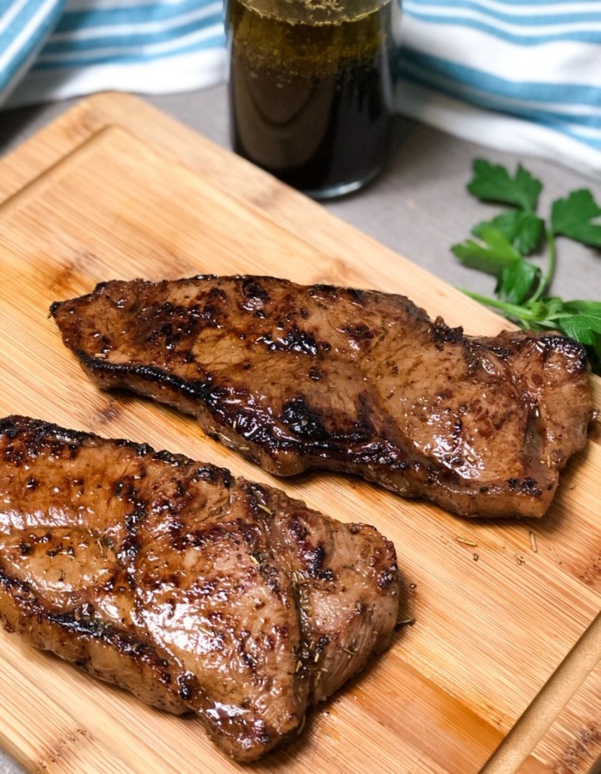 A wooden chopping board is on a table in front of a full glass and some herbs. On the board are 2 cooked flank steaks