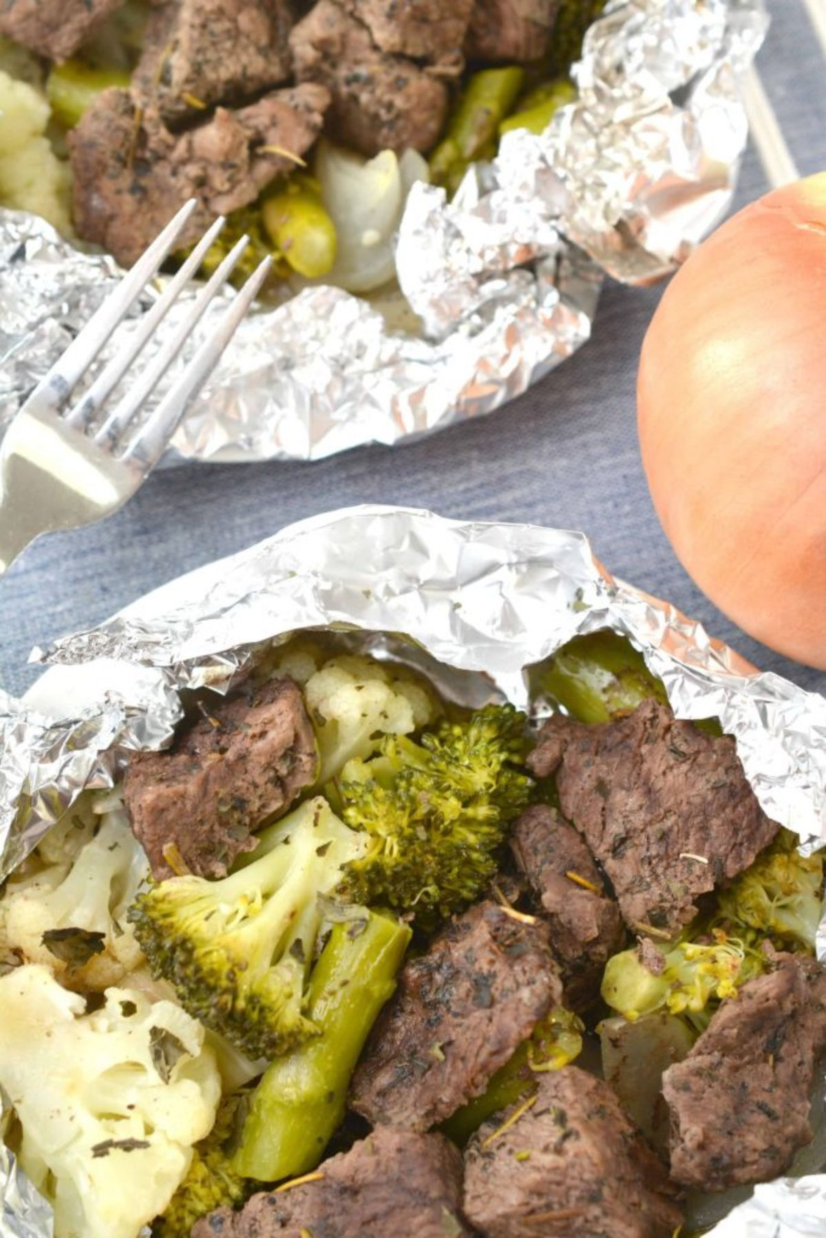2 foil pockets are on a countertop, slightly undone. Inside are steak bites and broccoli florets. There is the top of a fork digging into one pocket