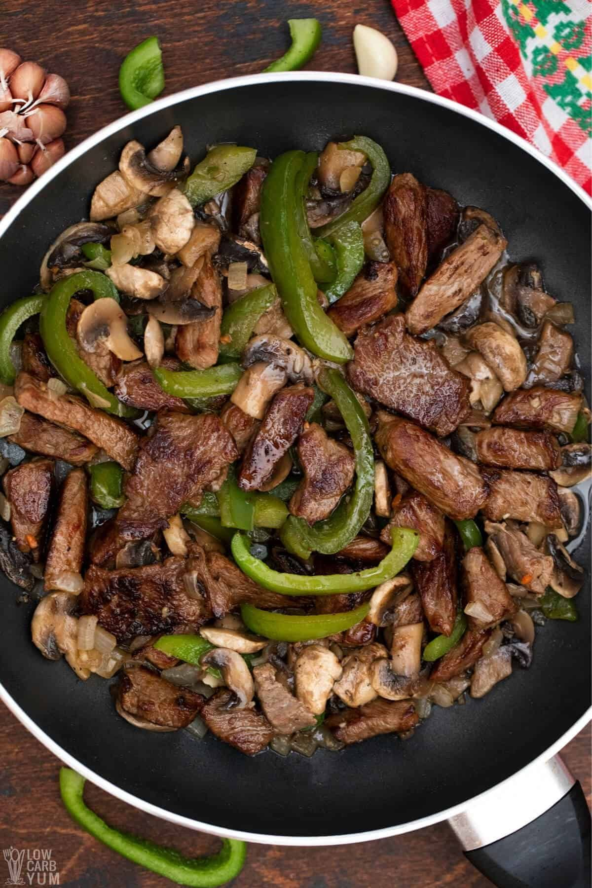 A top view of a skillet filled with steak slices, sliced mushrooms and sliced green peppers