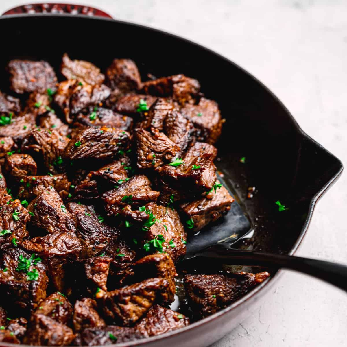 A partial shot of a skillet filled with steak bites and herbs