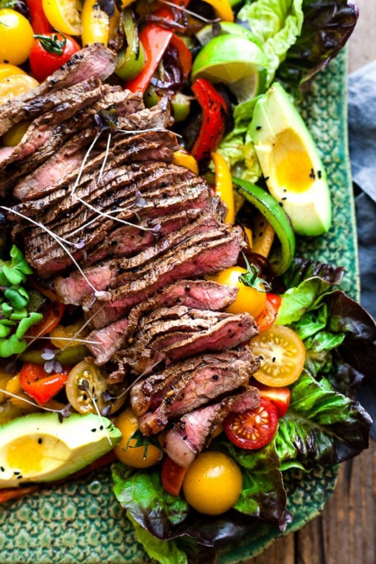 A partial shot of a green serving platter. On it are lettuce leaves, avocado, sliced peppers, halved yellow and red tomatoes, and sliced steak
