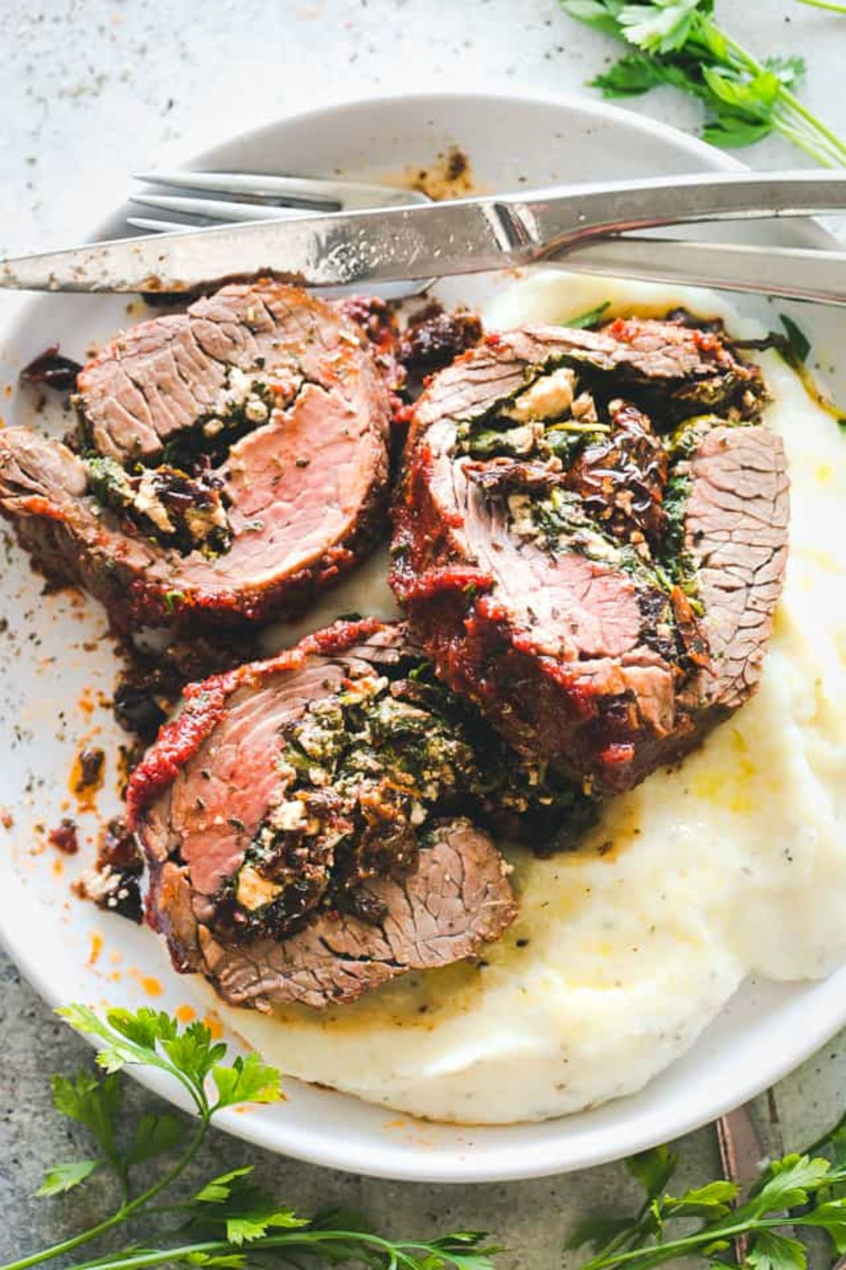 A white plate holds 3 slices of stuffed flank steak on a bed of mash. A knife and fork are at the top of the plate resting on each other. Herbs are scattered around