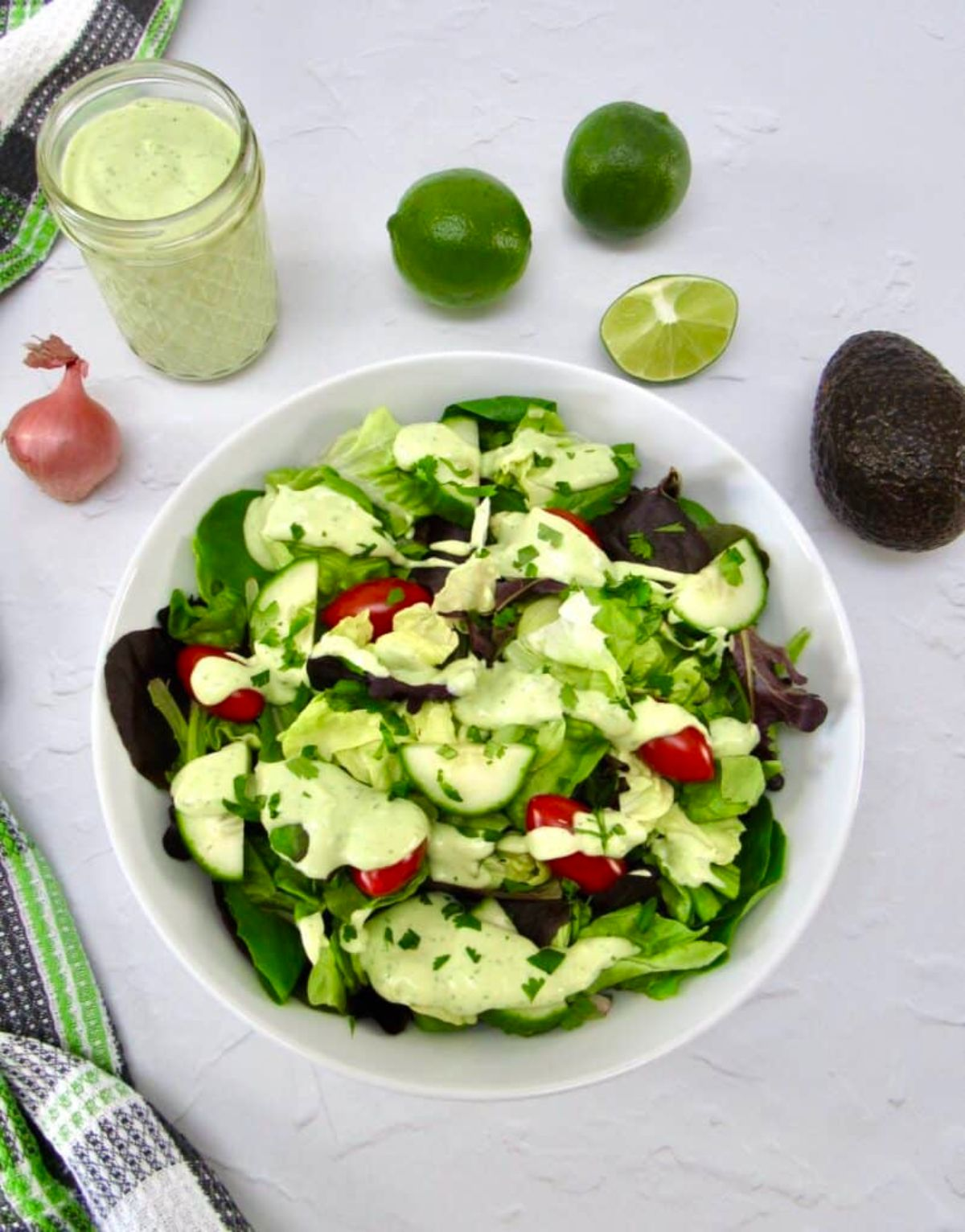 On a white marble countertop is a white round bowl with a green salad, drizzled with green dressing. Around the bowl is a glass jar of dressing, limes and lime wedges, a shallot, and an avocado