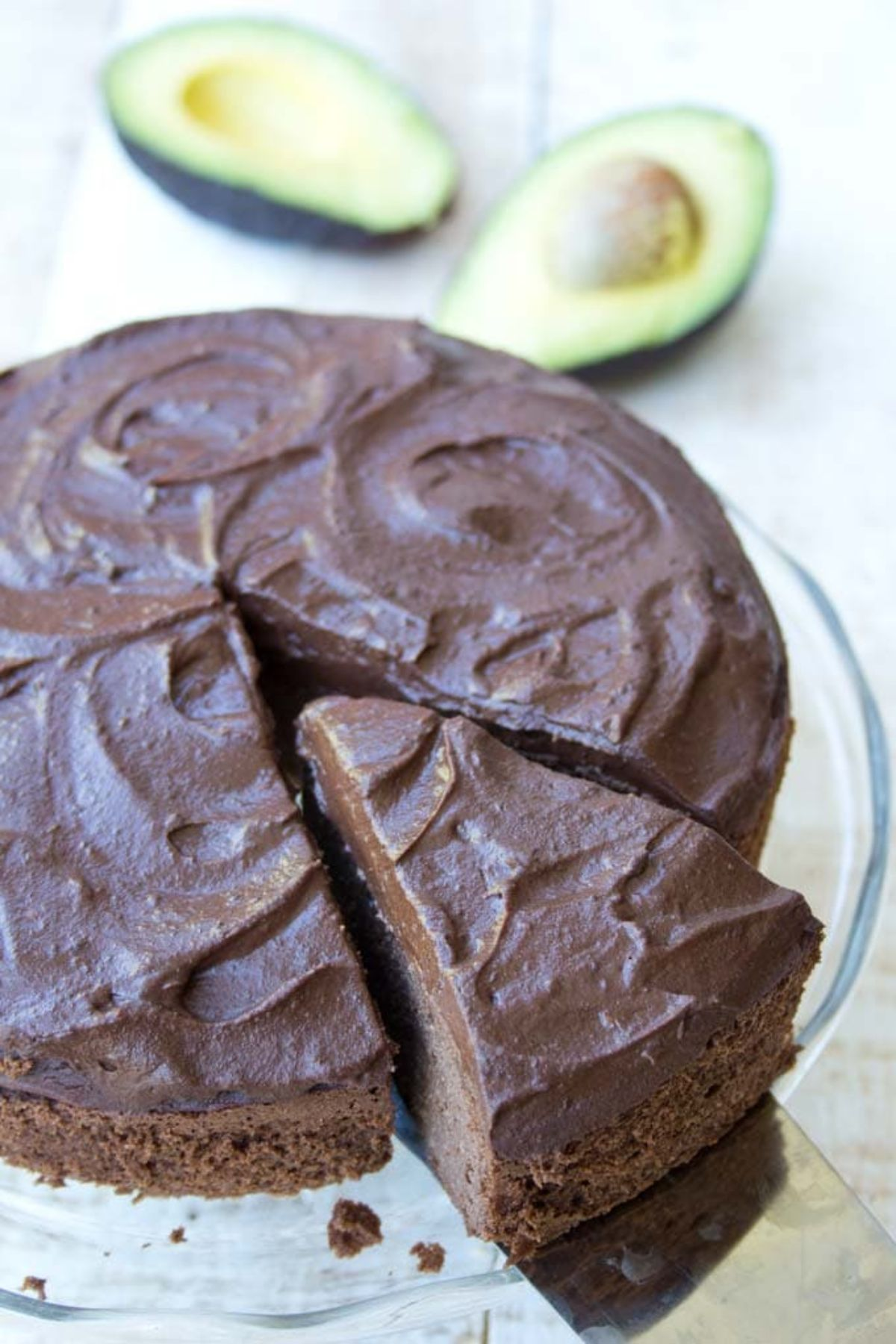 On a glass cake stand is a chocolate ckae with one slice cut out of it. Behind are 2 avocado halves
