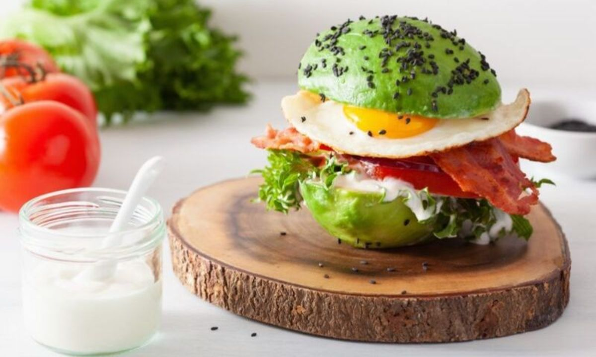 On a white countertop is a slice of tree trunk. On top of this is a peeled avocado, cut in half and acting as a burger bun around slices of bacon, a fried egg, and some lettuce leaves. To the left is a glass jar of sauce, tomatoes and a head of lettuce