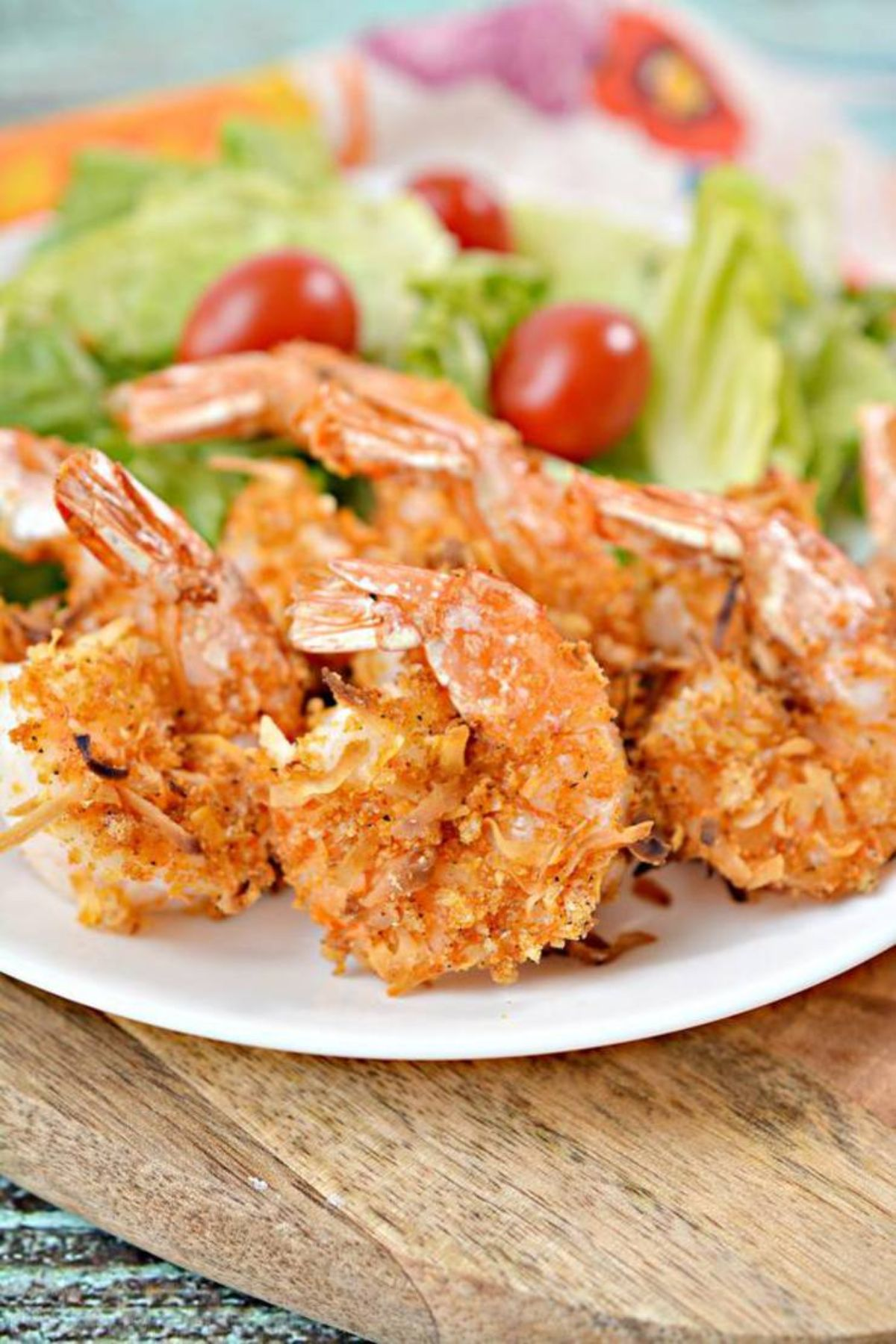 On a partially seen wooden board is a whote plate fll of coconut shrimp in front of a lettuce and cherry tomato salad