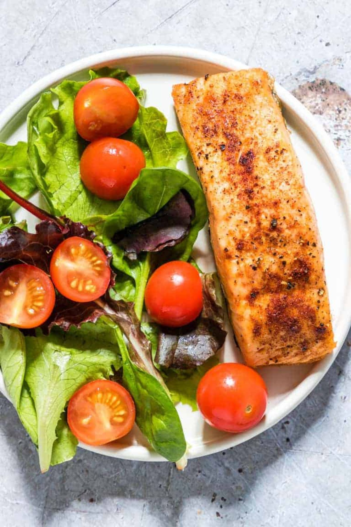 A round white plate holds a salmon fillet and a salad of green leaves and halved cherry tomatoes