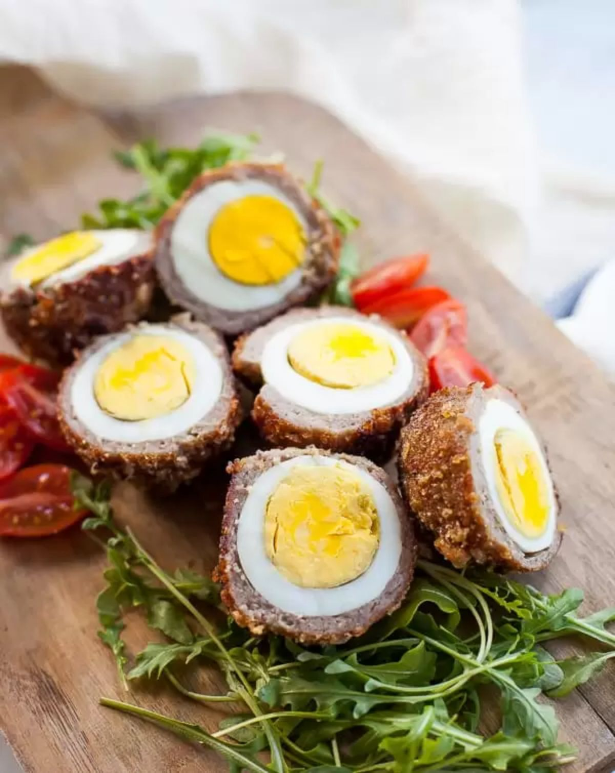 A wooden chopping board has 3 halved scotch eggs on a bed of arugala leaves and tomatoes