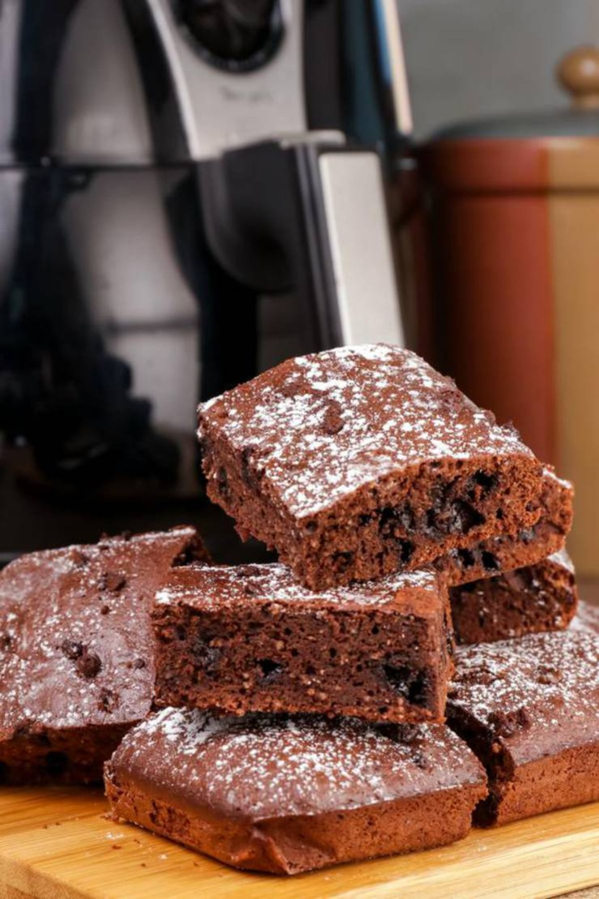In front of an air fryer on a wooden board is a pile of chocolate brownies